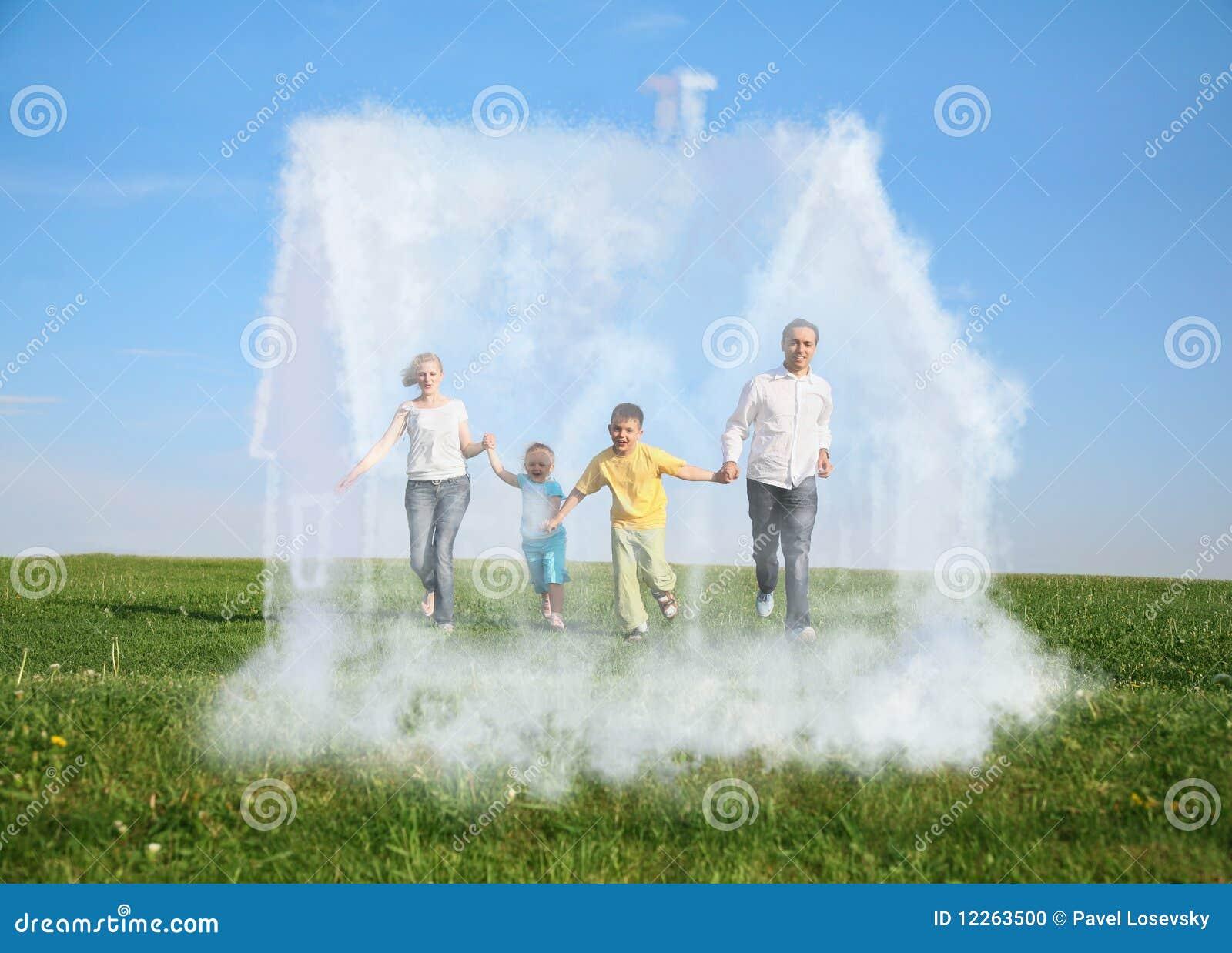 Família que funciona na grama e na casa ideal