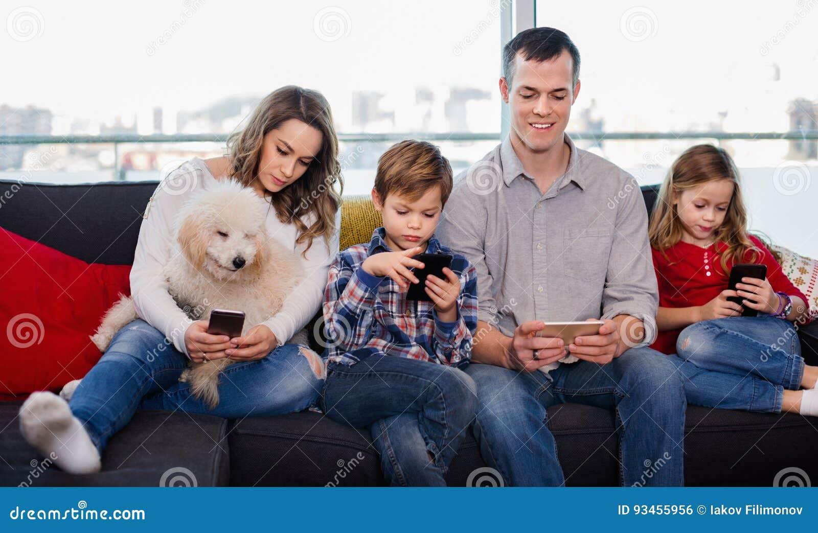 Família que joga com seus smartphones junto em casa