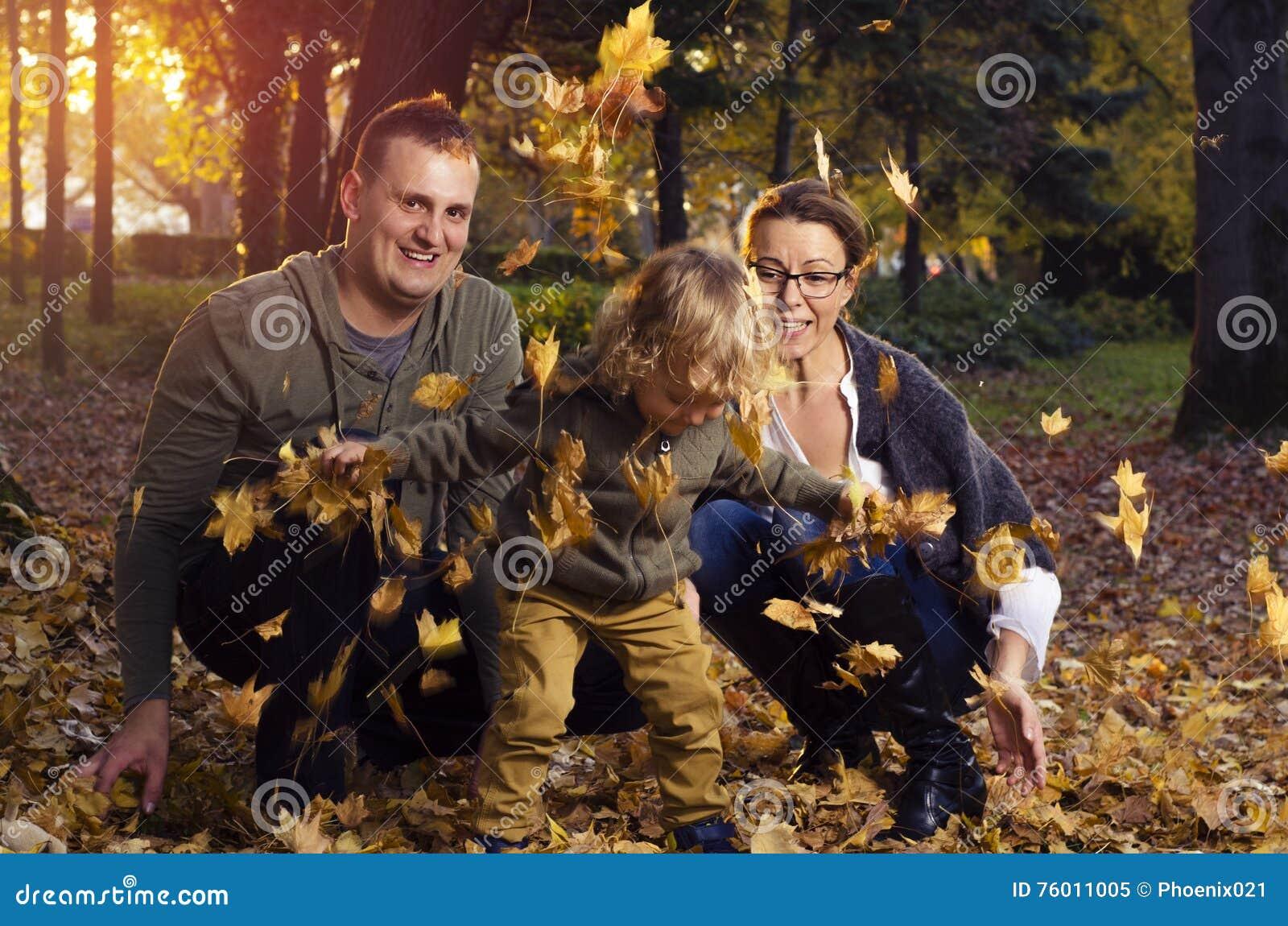 Família que joga nas folhas de outono