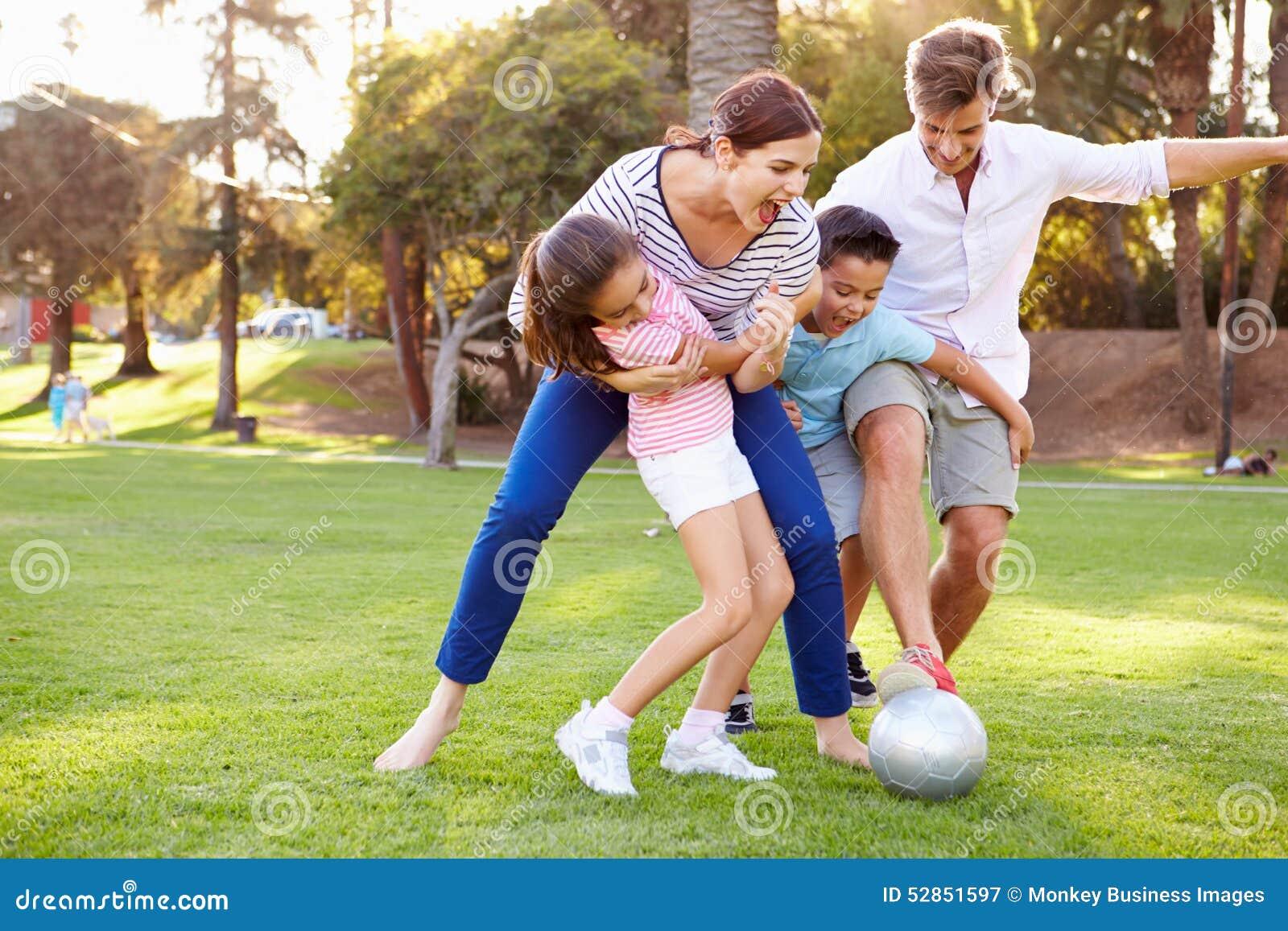 Família que joga o futebol no parque junto