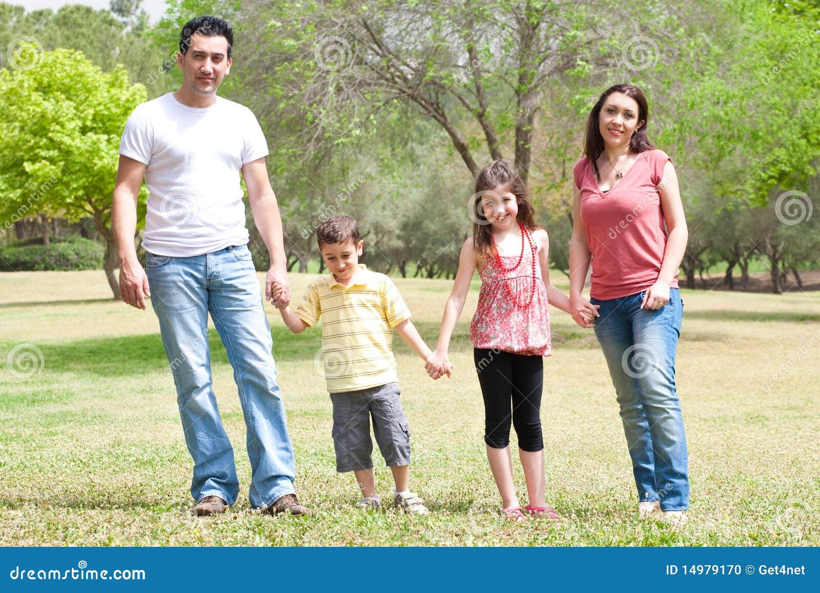 Família que levanta à câmera no parque