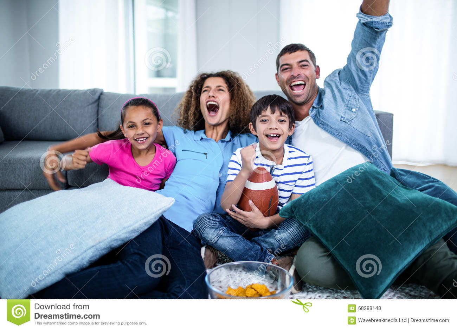 Família que olha o fósforo de futebol americano na televisão