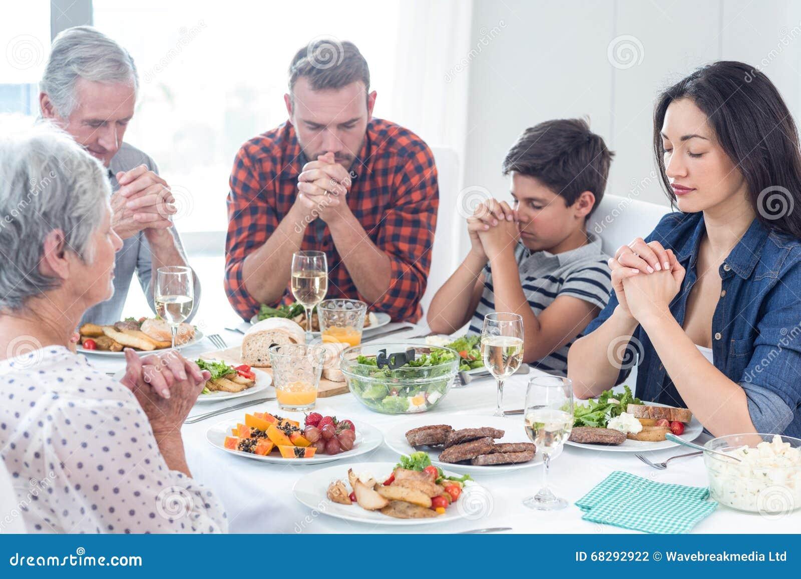 Família que reza junto antes da refeição