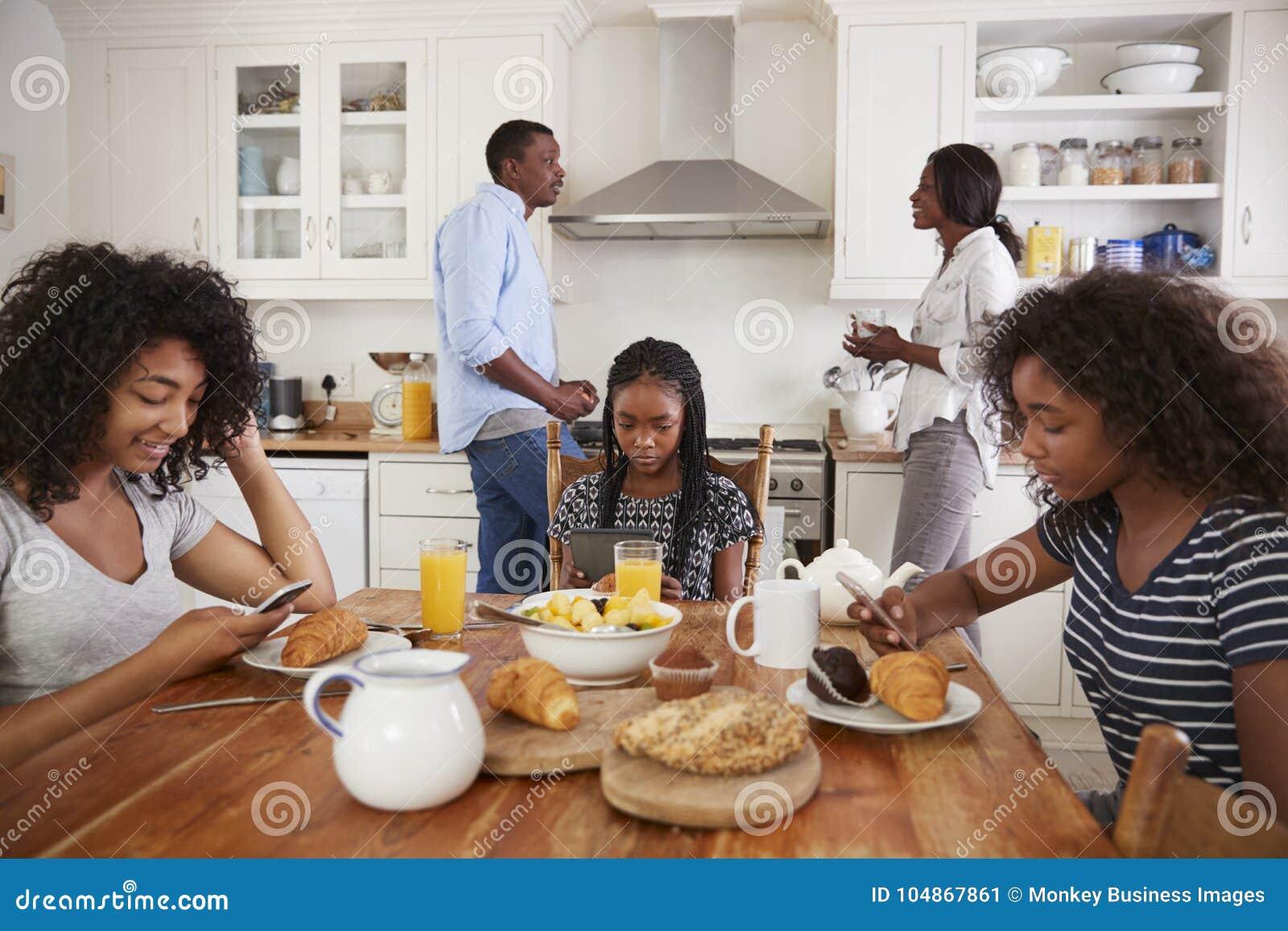 Família que senta-se em torno da tabela de café da manhã usando dispositivos de Digitas