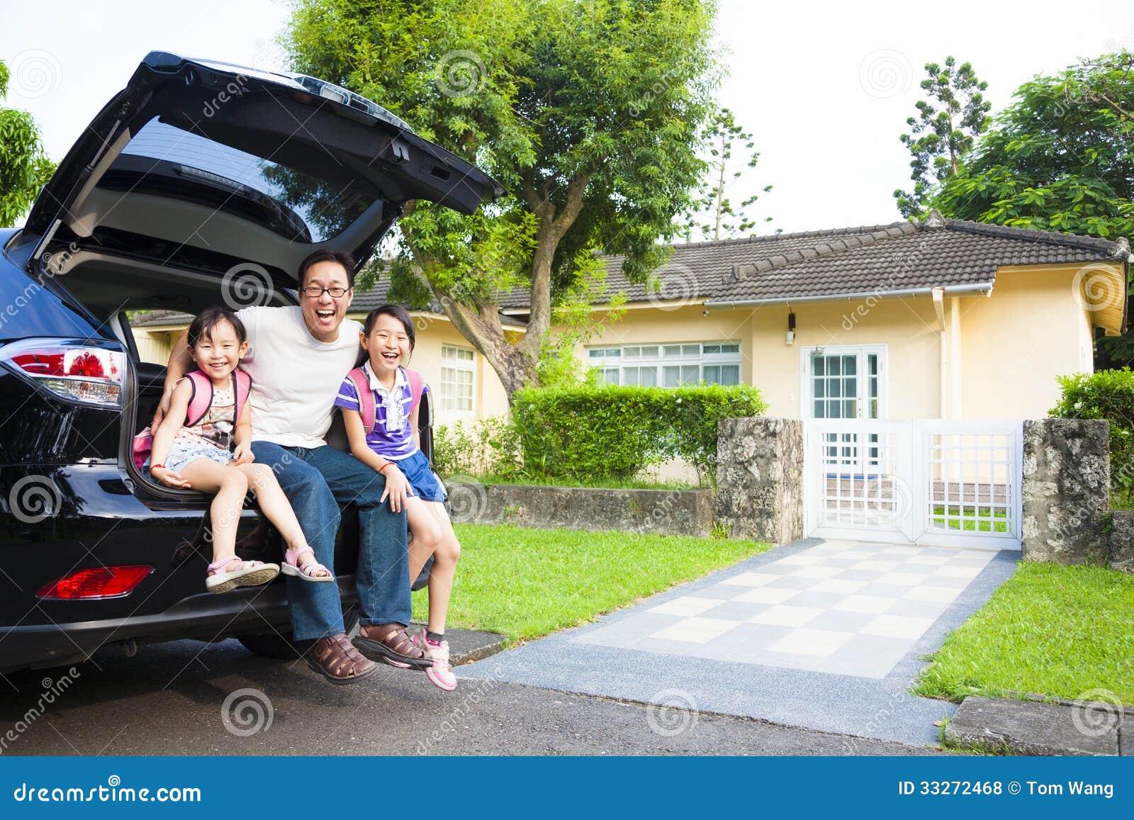 Família que senta-se no carro e em sua casa atrás