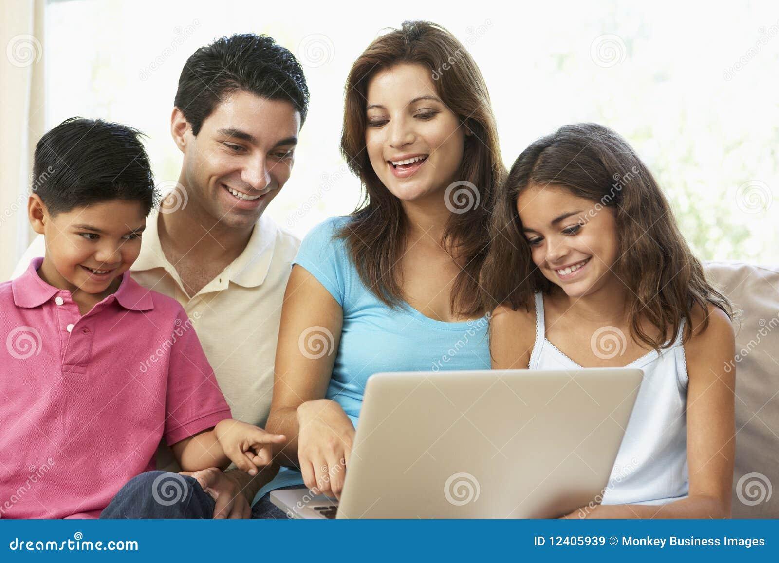 Família que senta-se no sofá em casa com portátil