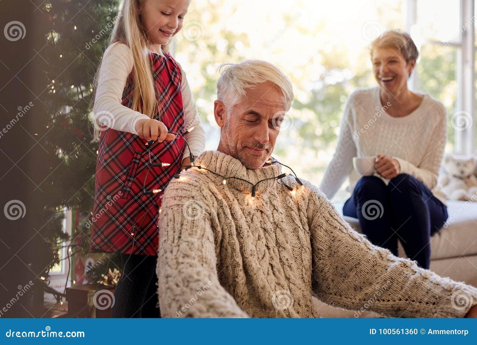 Família que tem o divertimento ao decorar a casa durante o Natal