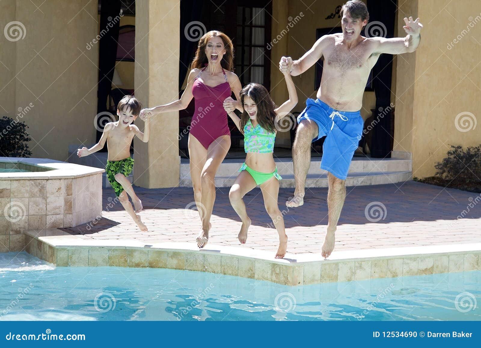 Família que tem o divertimento saltar na piscina