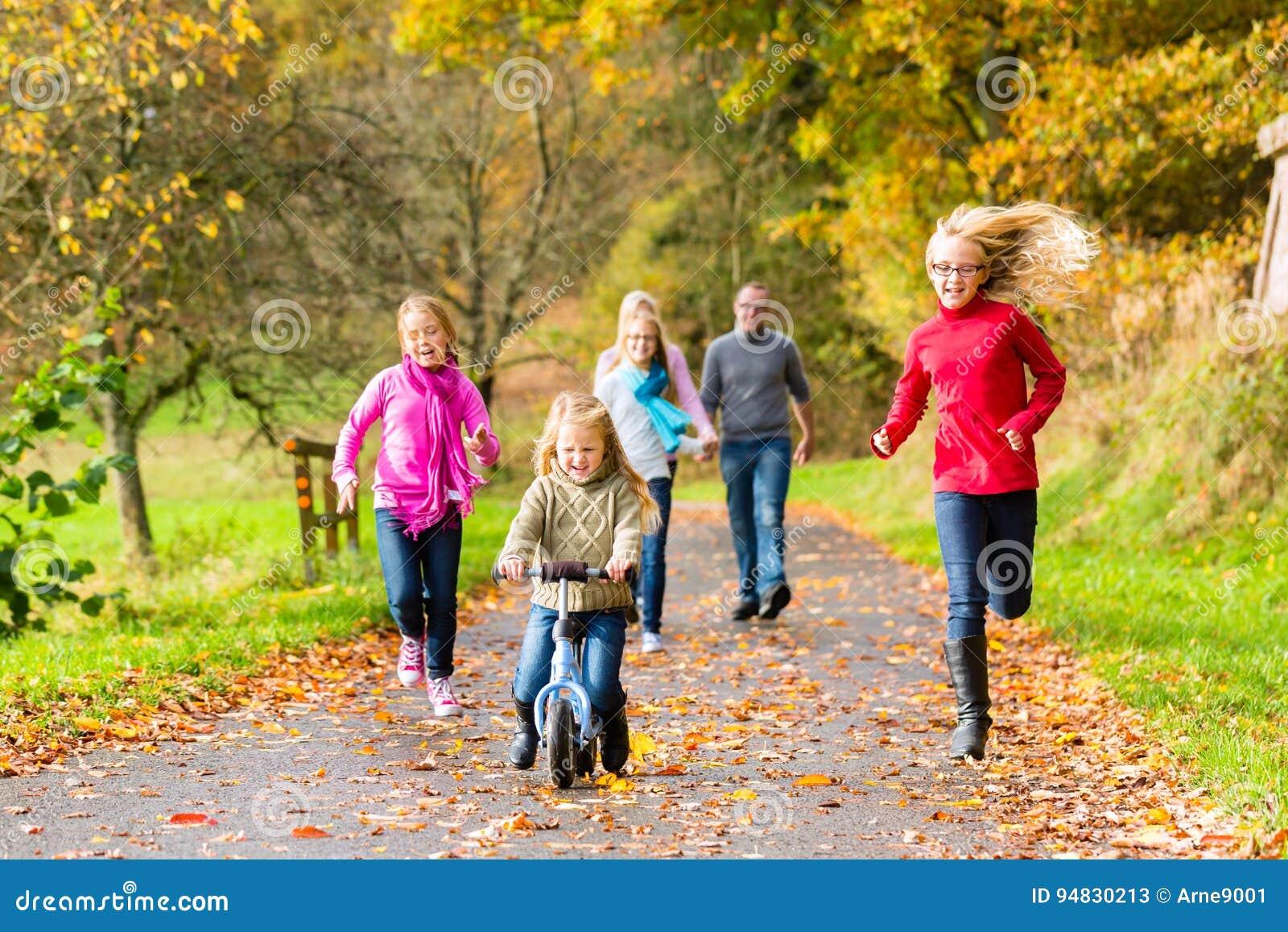 Família que toma a caminhada na floresta da queda do outono