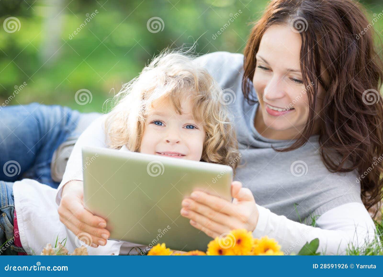 Família que usa o PC da tabuleta fora