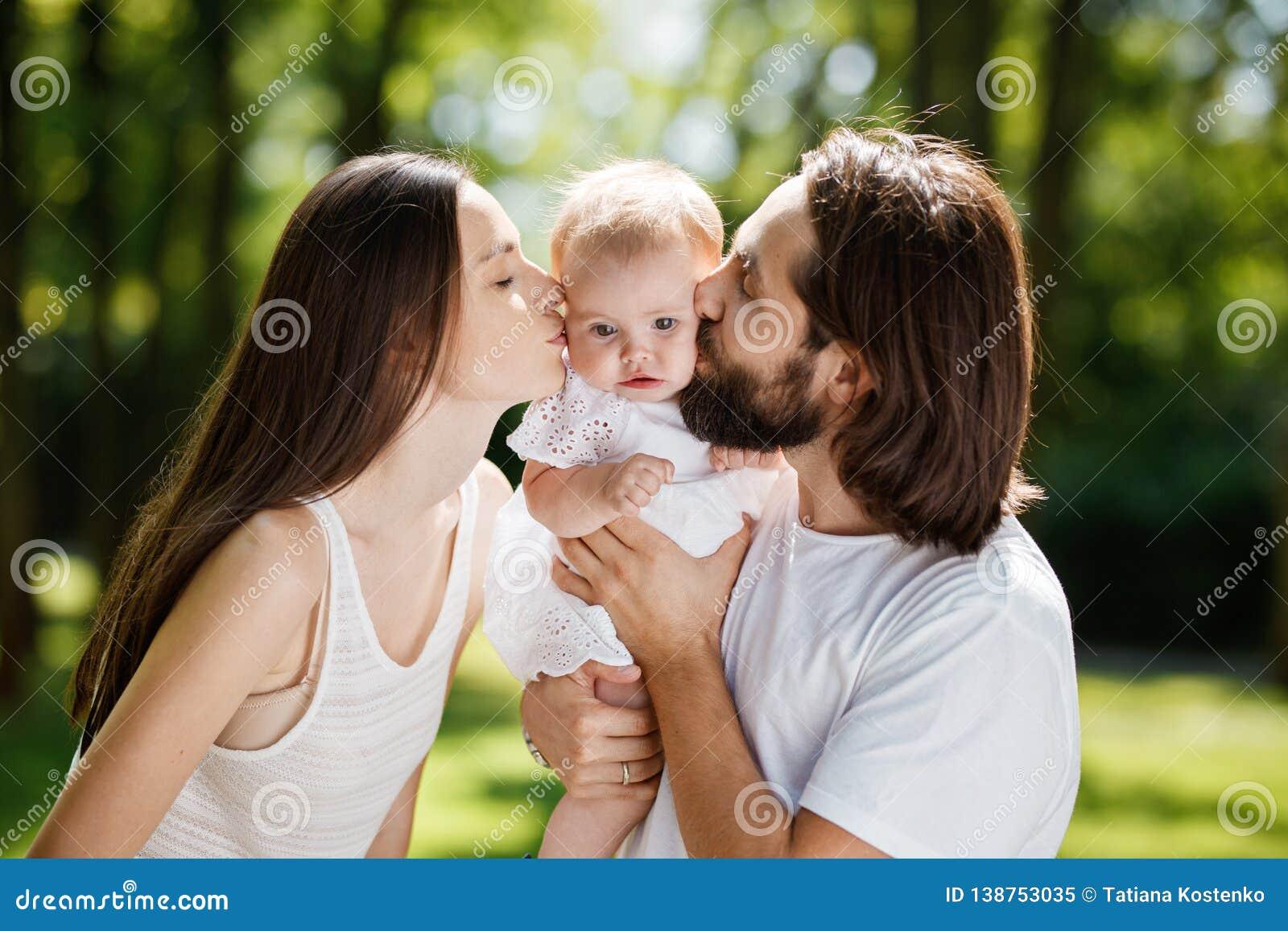 Família romântica no ar livre A morena nova e seu marido estão beijando sua filha pequena de encantamento