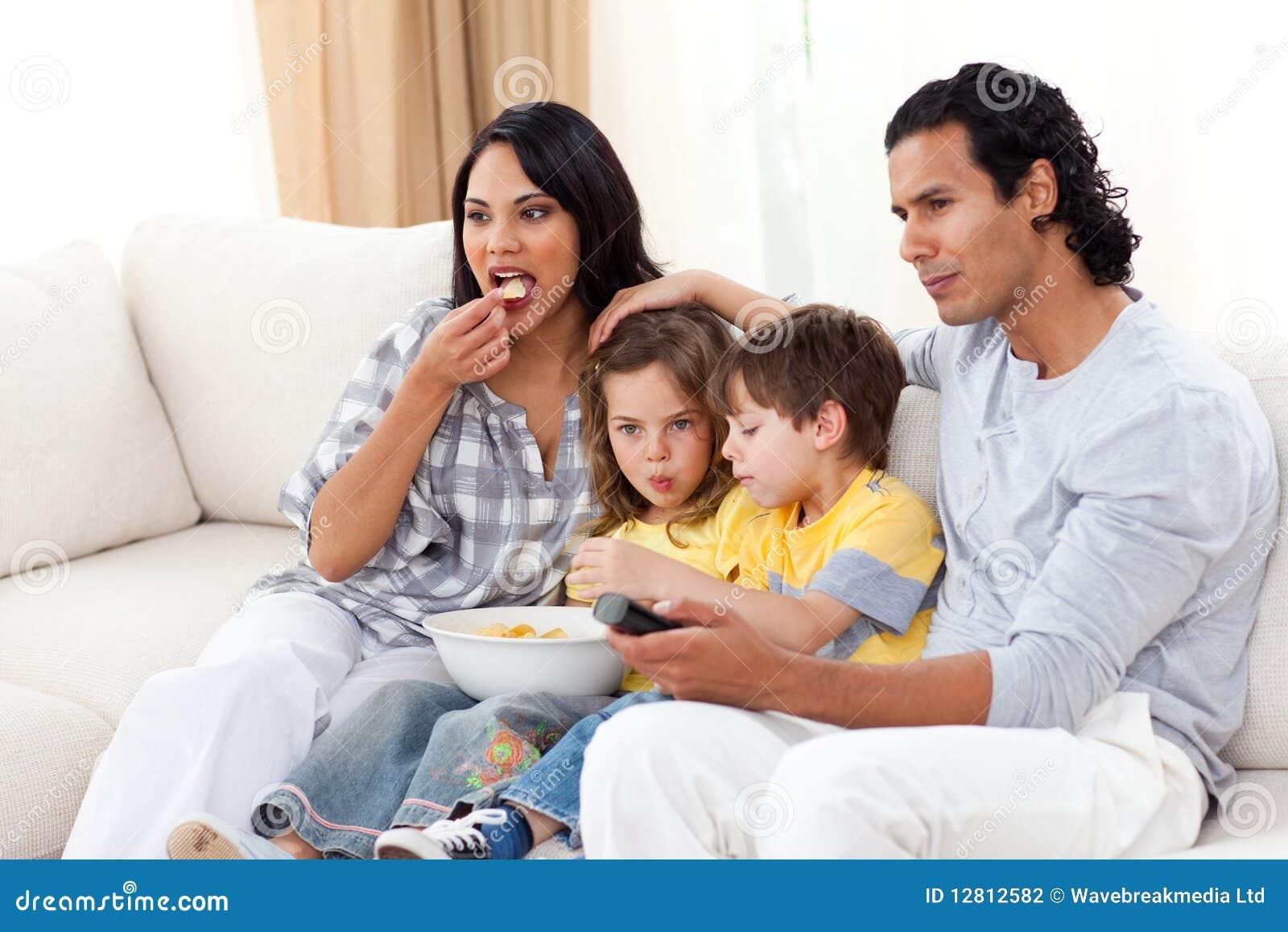 Família vívida que presta atenção à tevê e que come microplaquetas