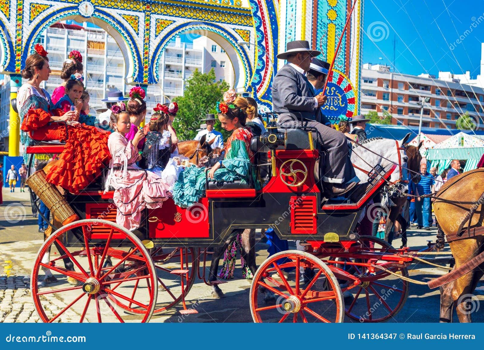 Famílias espanholas no vestido tradicional e colorido que viaja no transportes puxados a cavalo em April Fair, feira de Sevilha