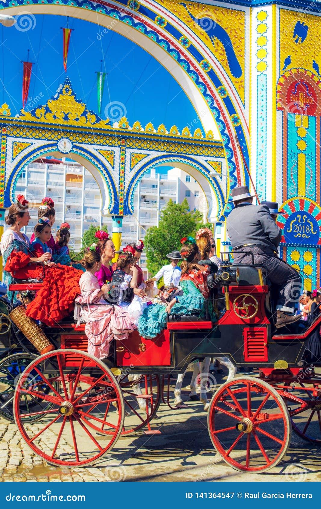 Famílias espanholas no vestido tradicional e colorido que viaja no transportes puxados a cavalo em April Fair