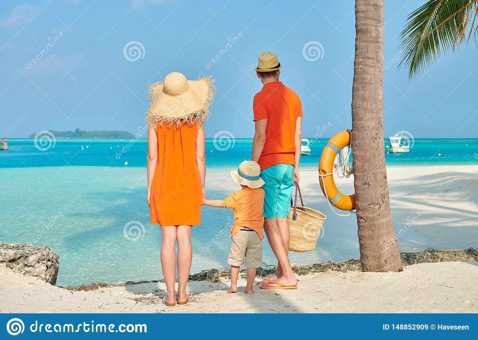 Fam?lia de tr?s na praia sob a palmeira