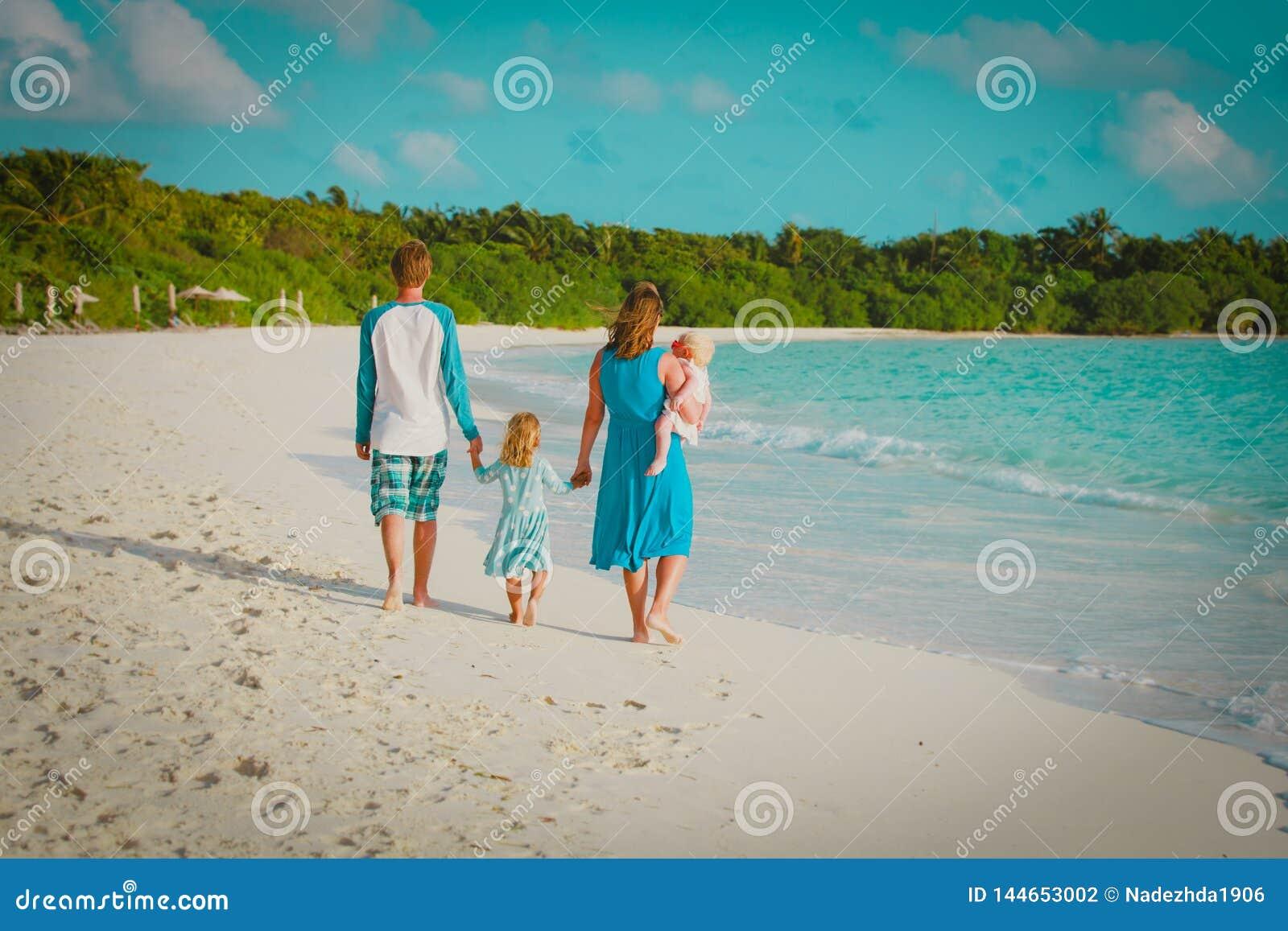 A fam?lia feliz com crian?as anda na praia tropical