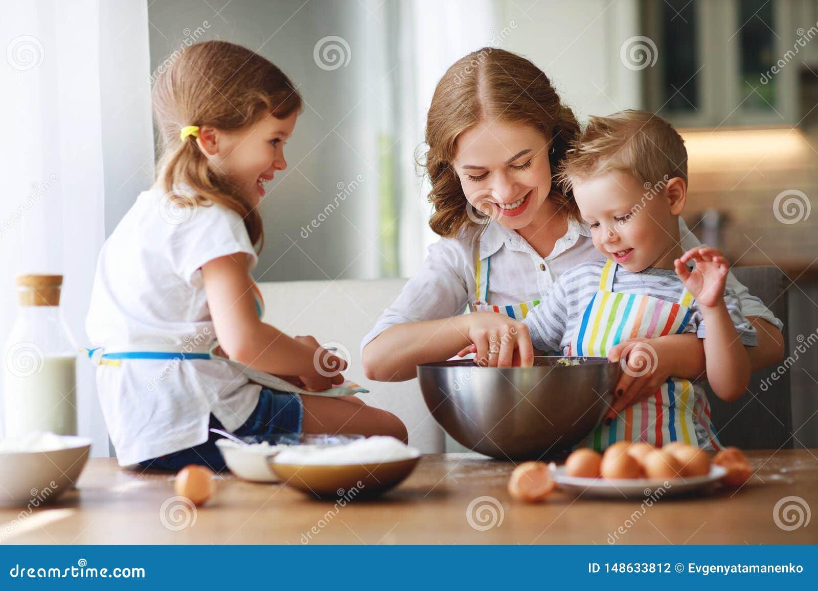 Fam?lia feliz na cozinha a m?e e as crian?as que preparam a massa, cozem cookies