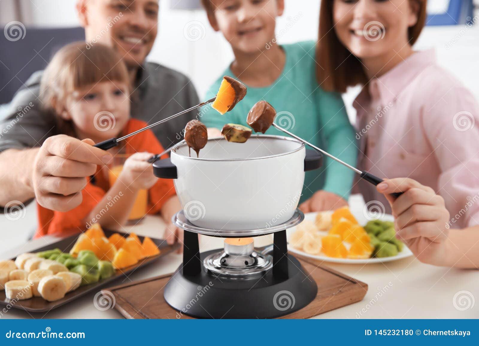 Fam?lia feliz que aprecia o jantar do fondue em casa