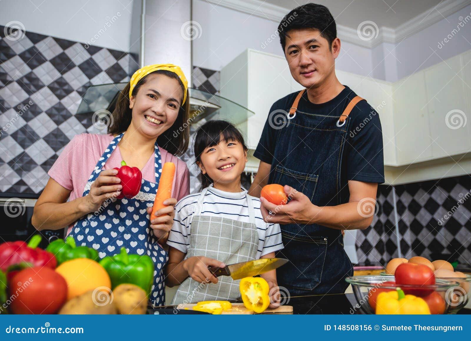 A fam?lia feliz tem o paizinho, a mam? e sua filha pequena cozinhando junto na cozinha