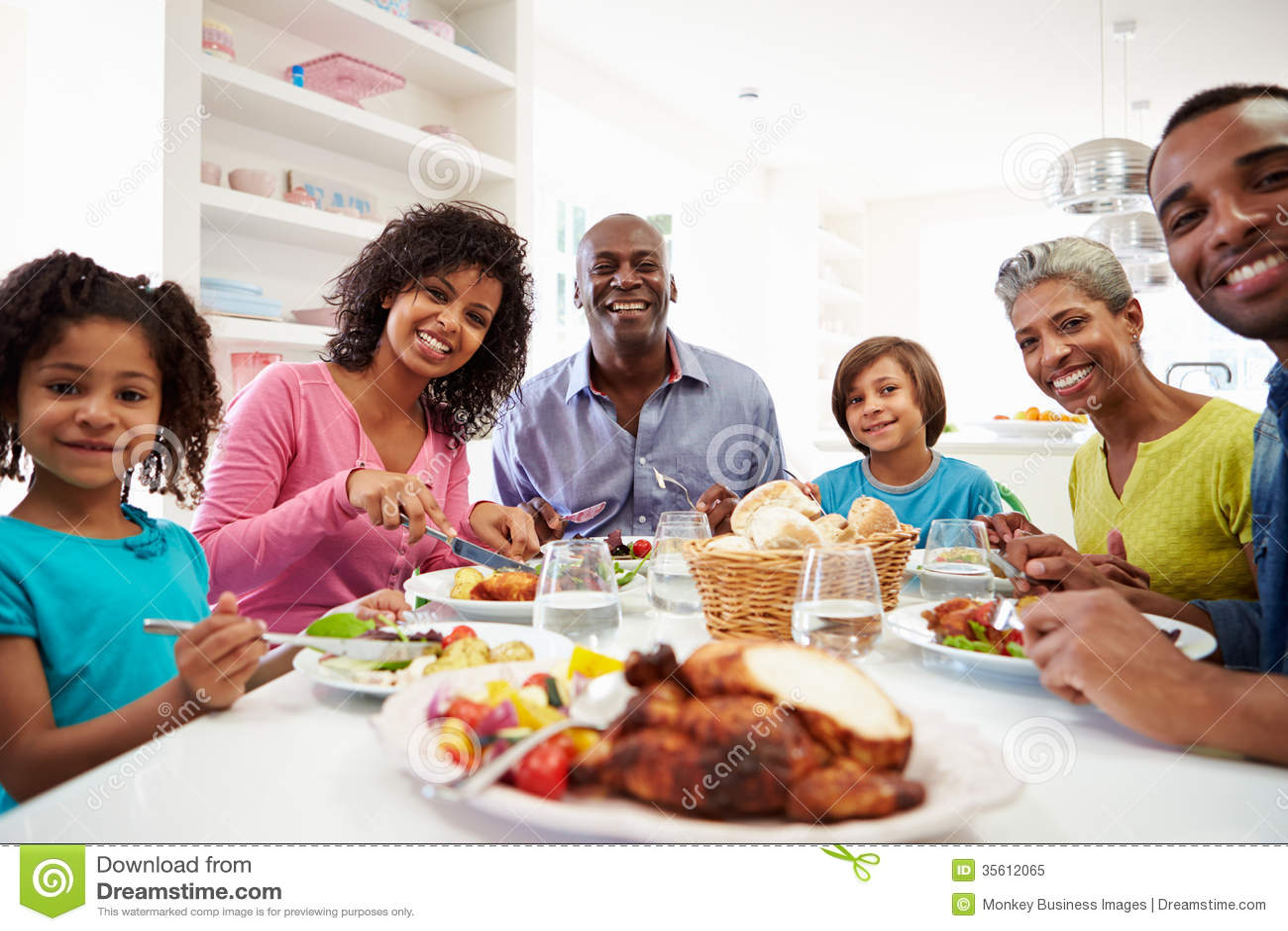 Famiglia afroamericana della multi generazione che mangia pasto a casa