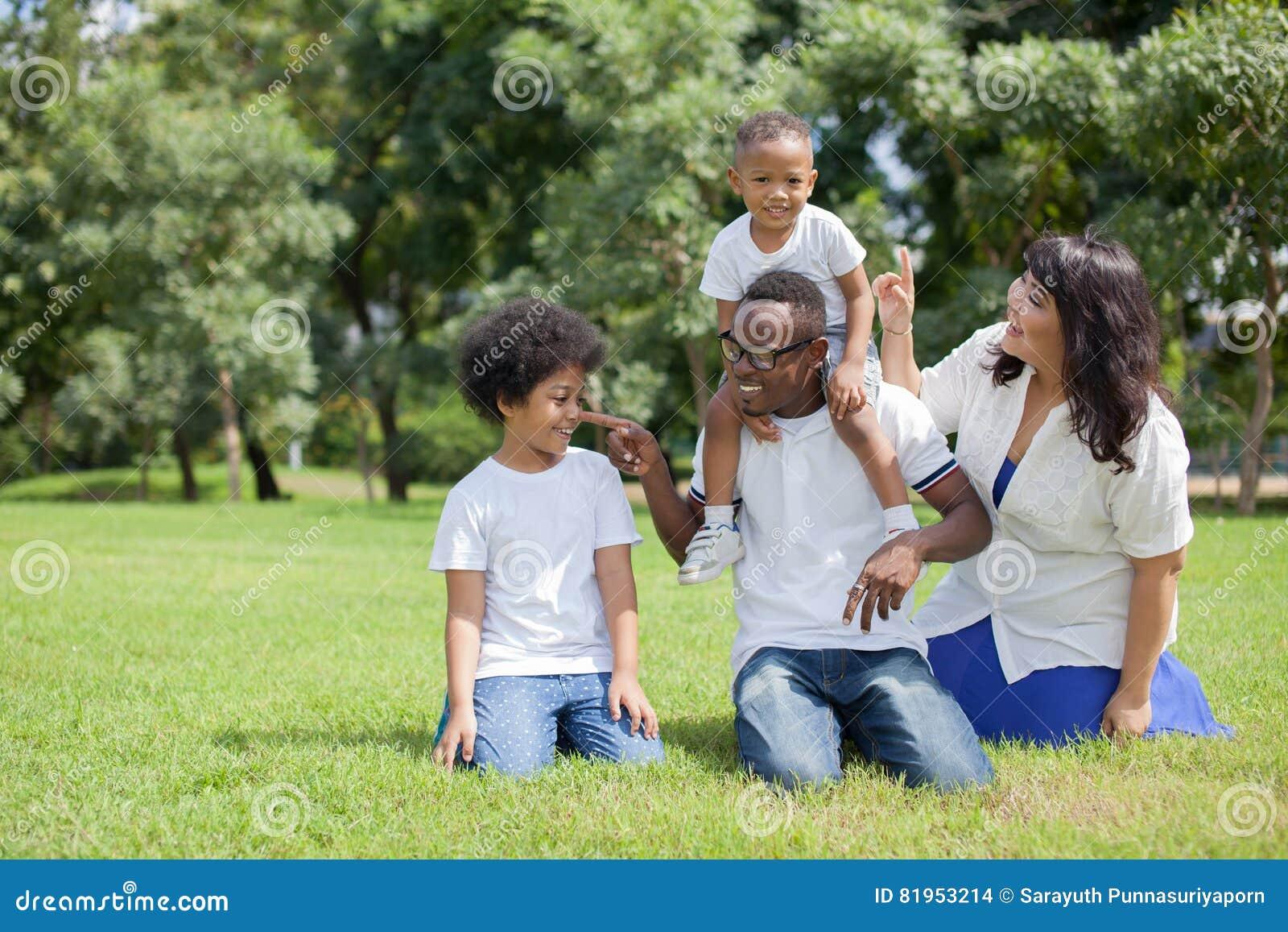 Famiglia afroamericana di fianco con la mummia asiatica che è a allegra