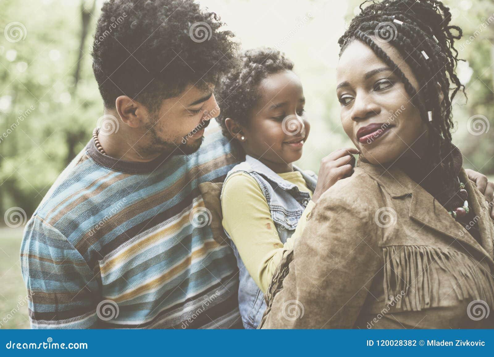 Famiglia afroamericana felice che gode nel holdin della madre e del parco