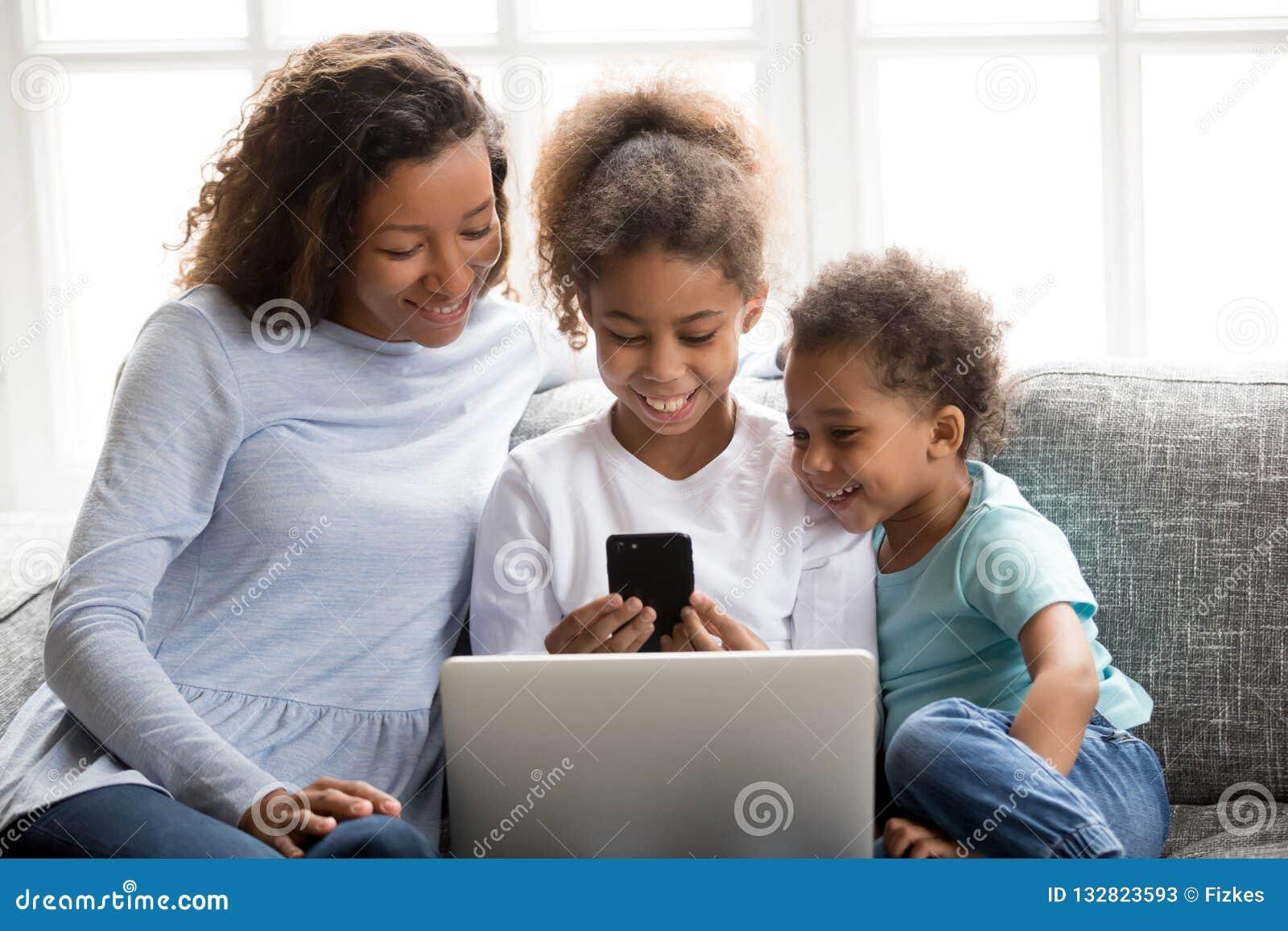 Famiglia afroamericana felice facendo uso dei dispositivi mobili insieme