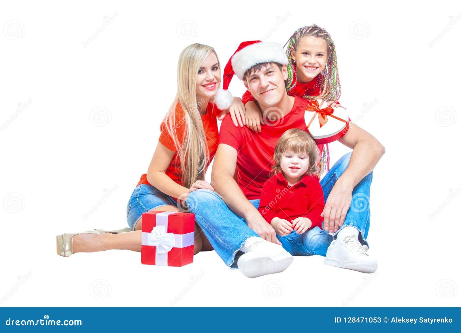 Famiglia al Natale Famiglia allegra in cappelli di Santa che esaminano macchina fotografica e che sorridono mentre isolato su bia