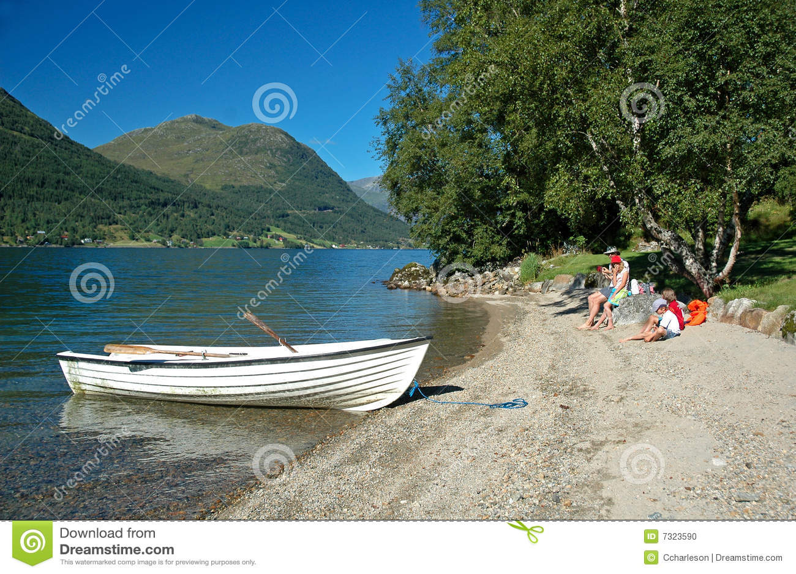 Famiglia alla riva del lago che ha picnic