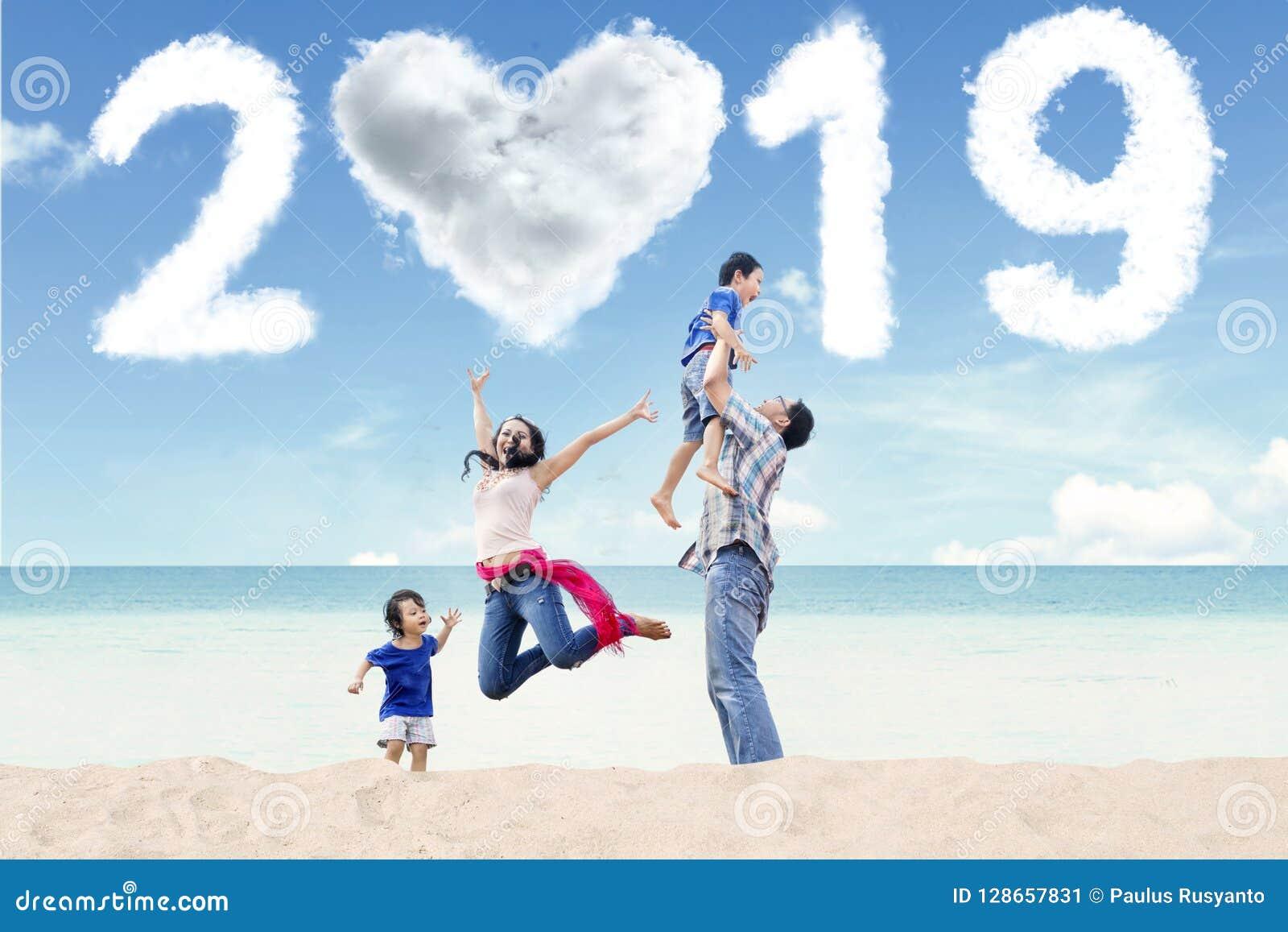 Famiglia asiatica con il numero 2019 sulla spiaggia