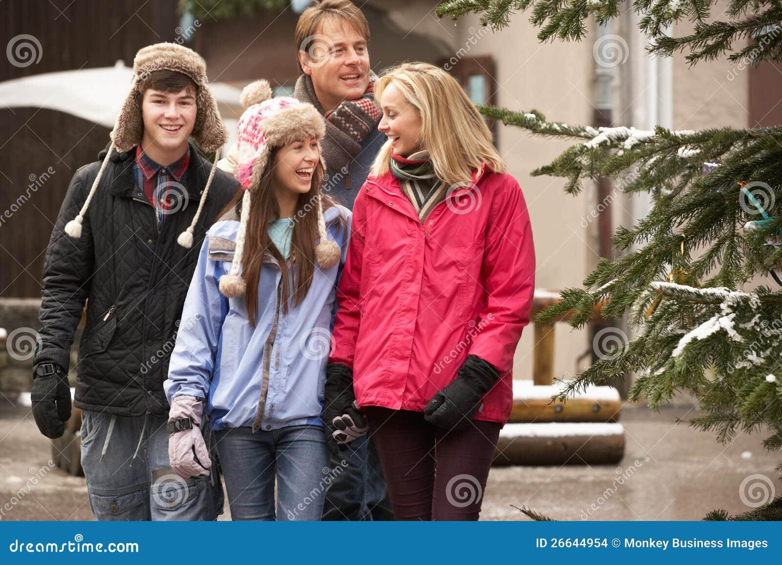 Famiglia che cammina lungo la via della città nella stazione sciistica