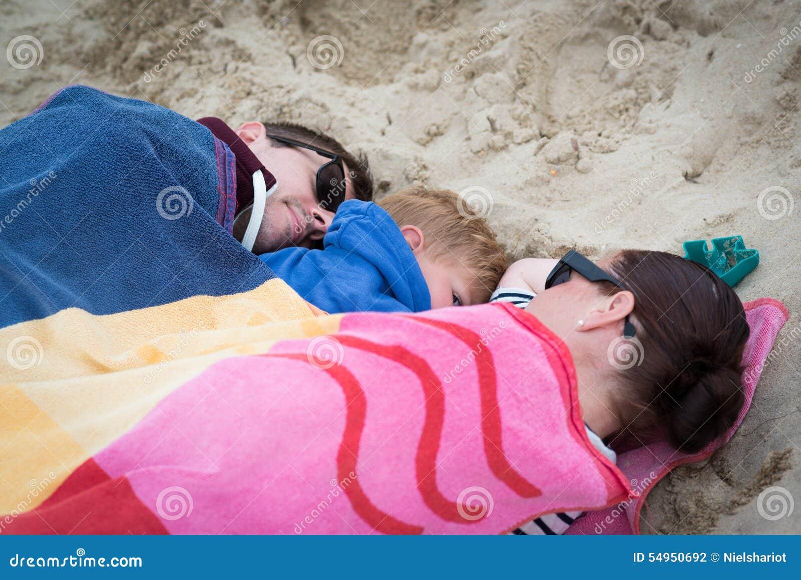 Famiglia che dorme sulla spiaggia fredda