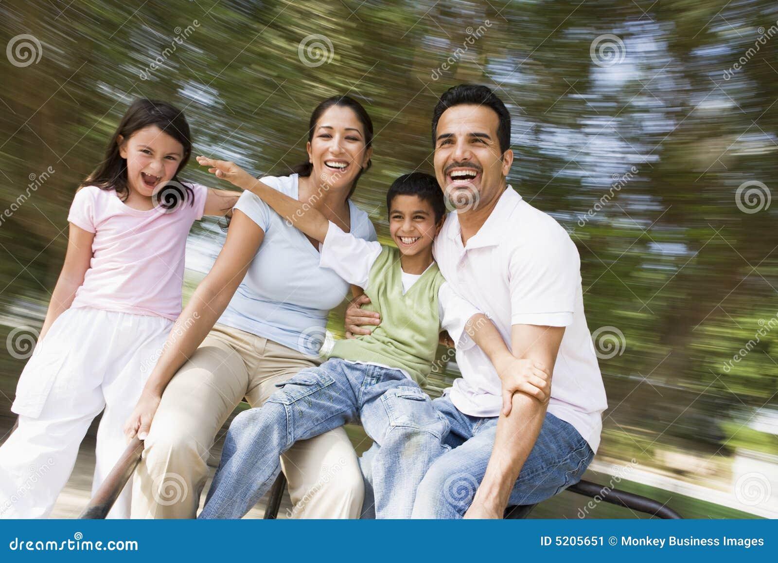 Famiglia che ha divertimento sulla rotonda di filatura