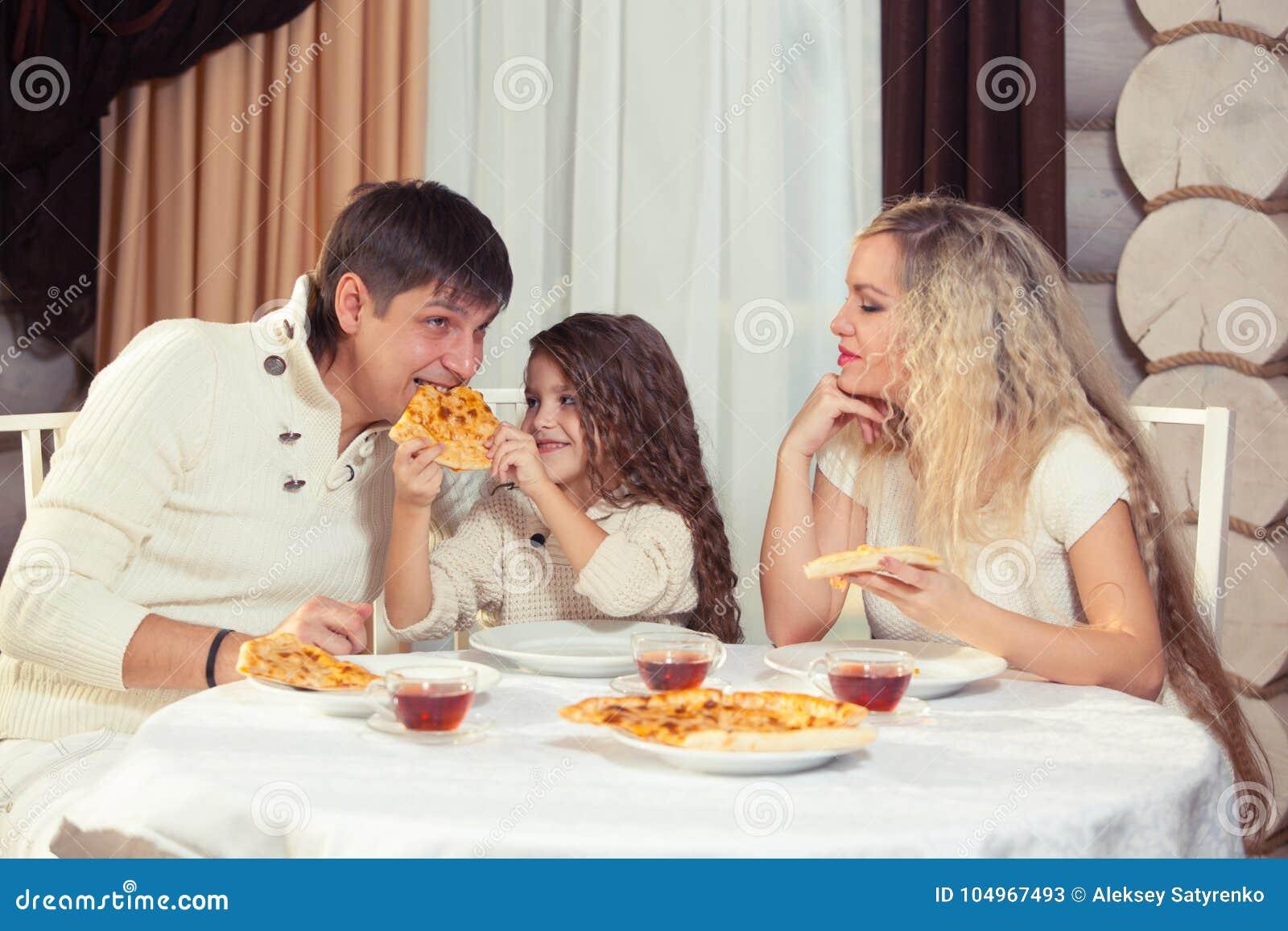Famiglia che mangia cena ad un tavolo da pranzo tavola for Tavola da pranzo in legno