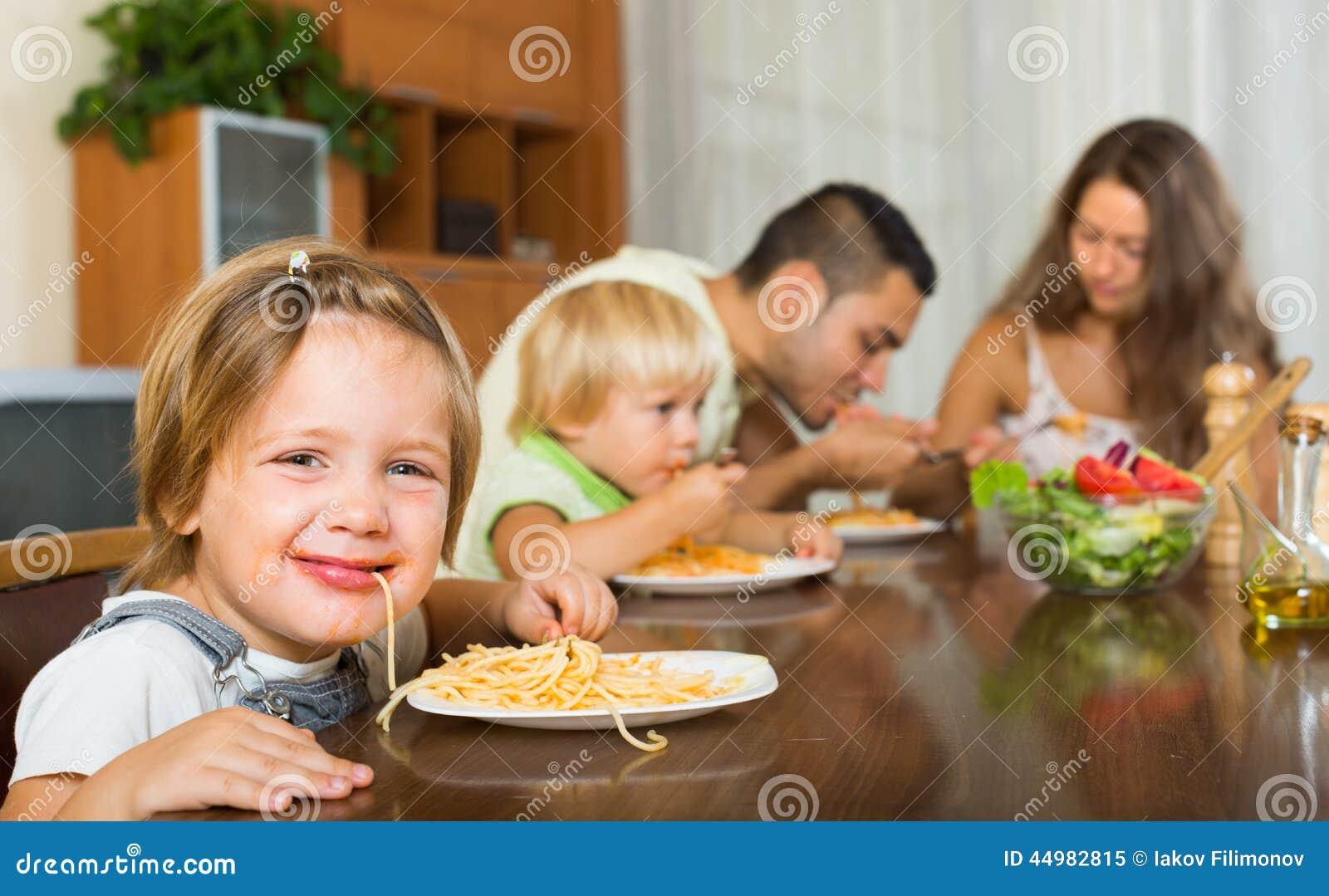Giovane famiglia con i bambini allegri che mangiano con gli spaghetti