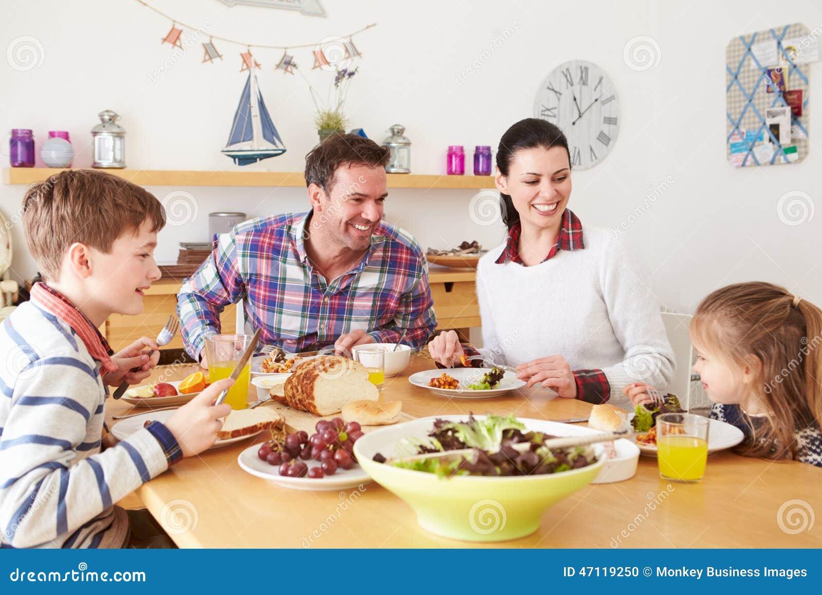 Famiglia che mangia pranzo al tavolo da cucina