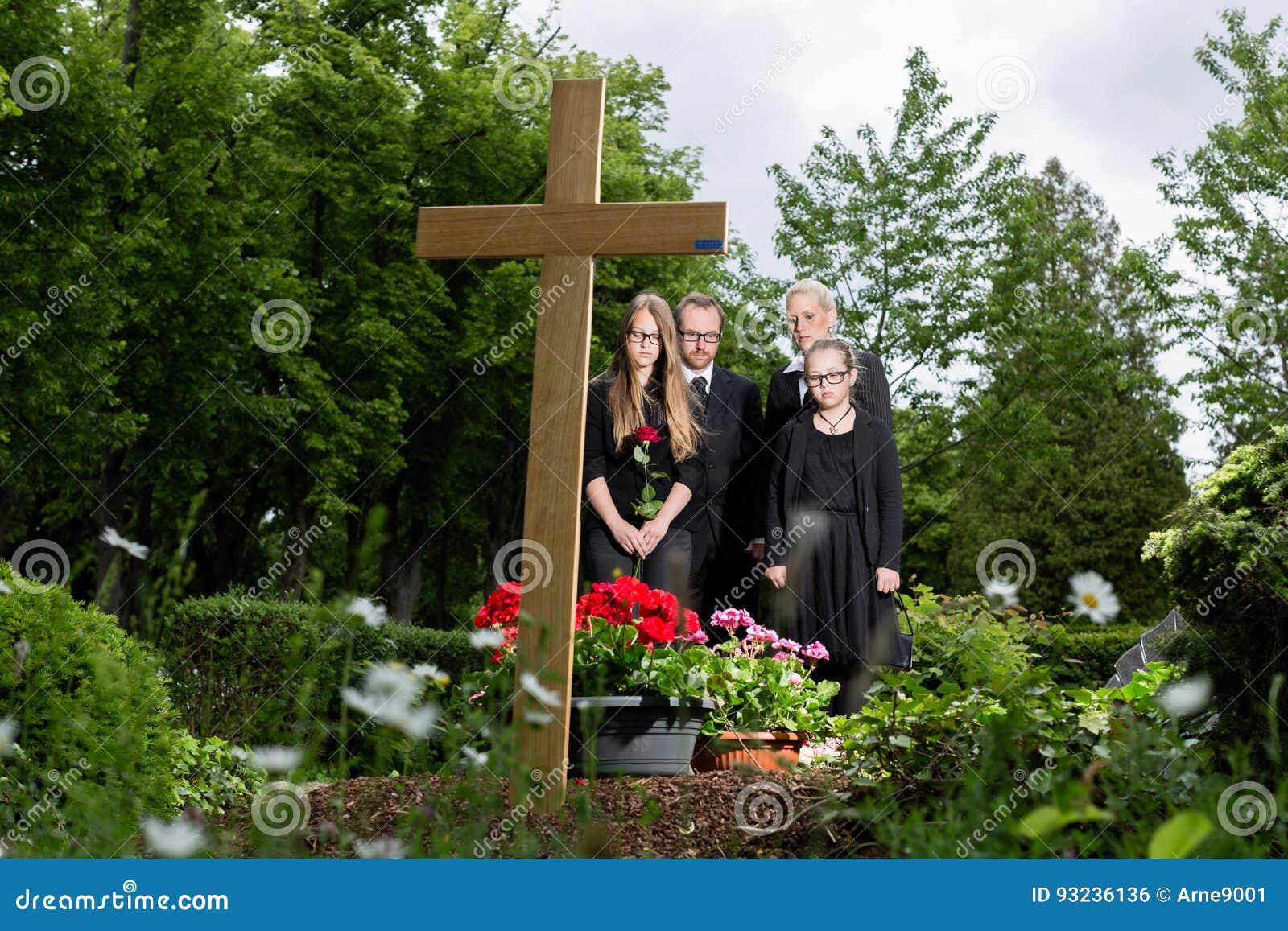 Famiglia che si addolora alla tomba sul cimitero