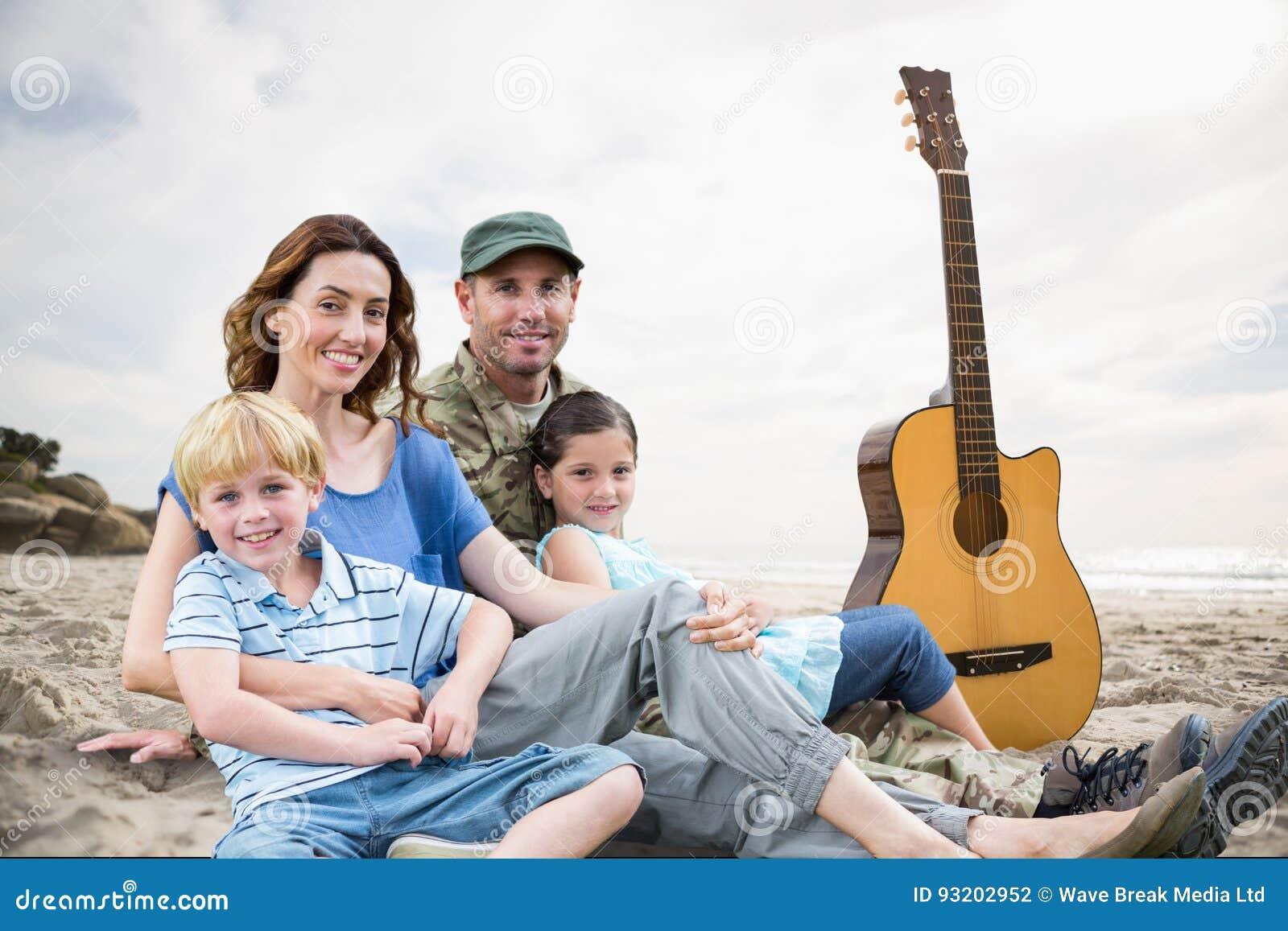 Famiglia che si siede sulla sabbia con una chitarra contro il fondo della spiaggia