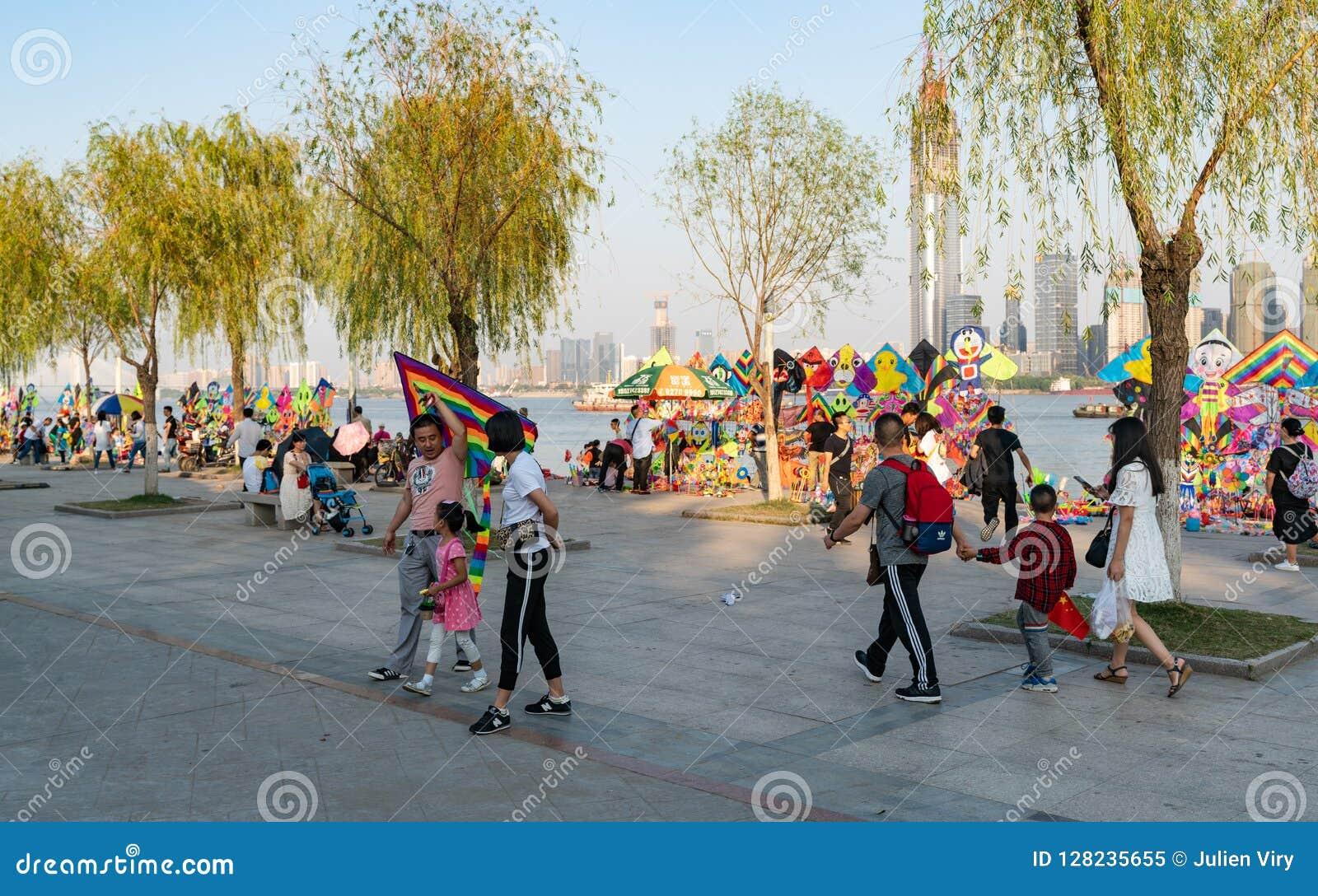 Famiglia cinese che tiene un aquilone e le stalle dell aquilone sul riversi di yangtze
