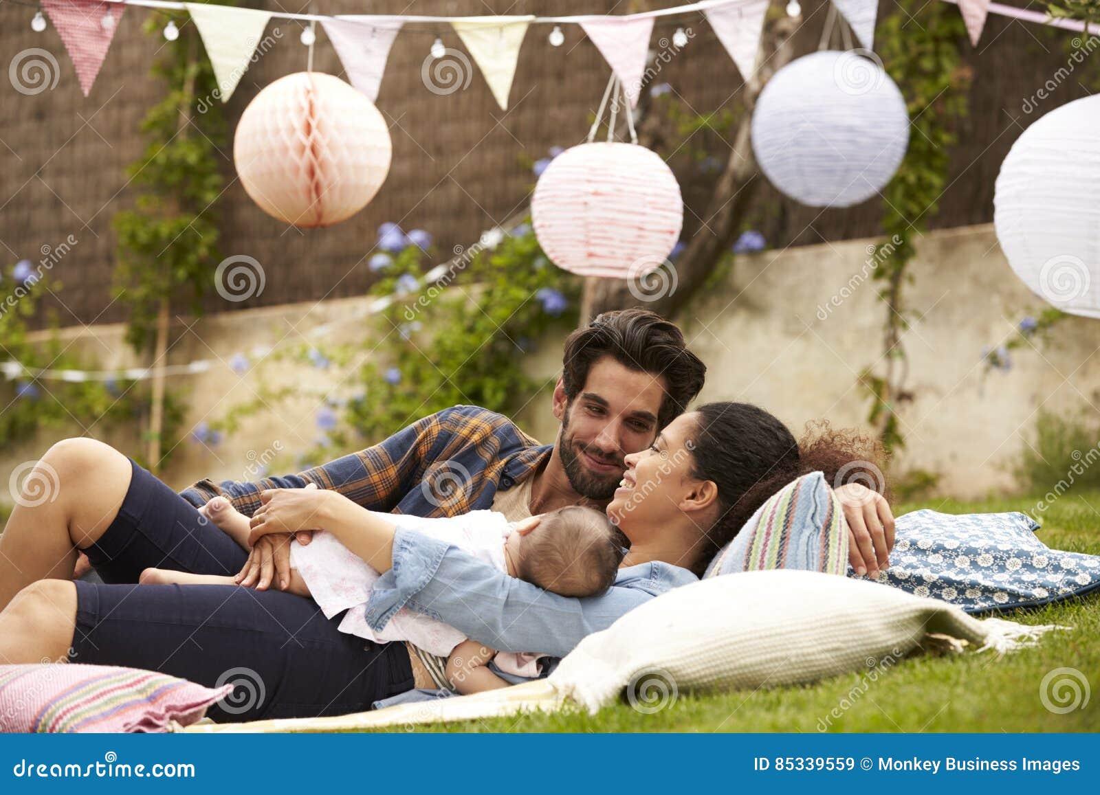 Famiglia con il bambino che si rilassa insieme sulla coperta in giardino
