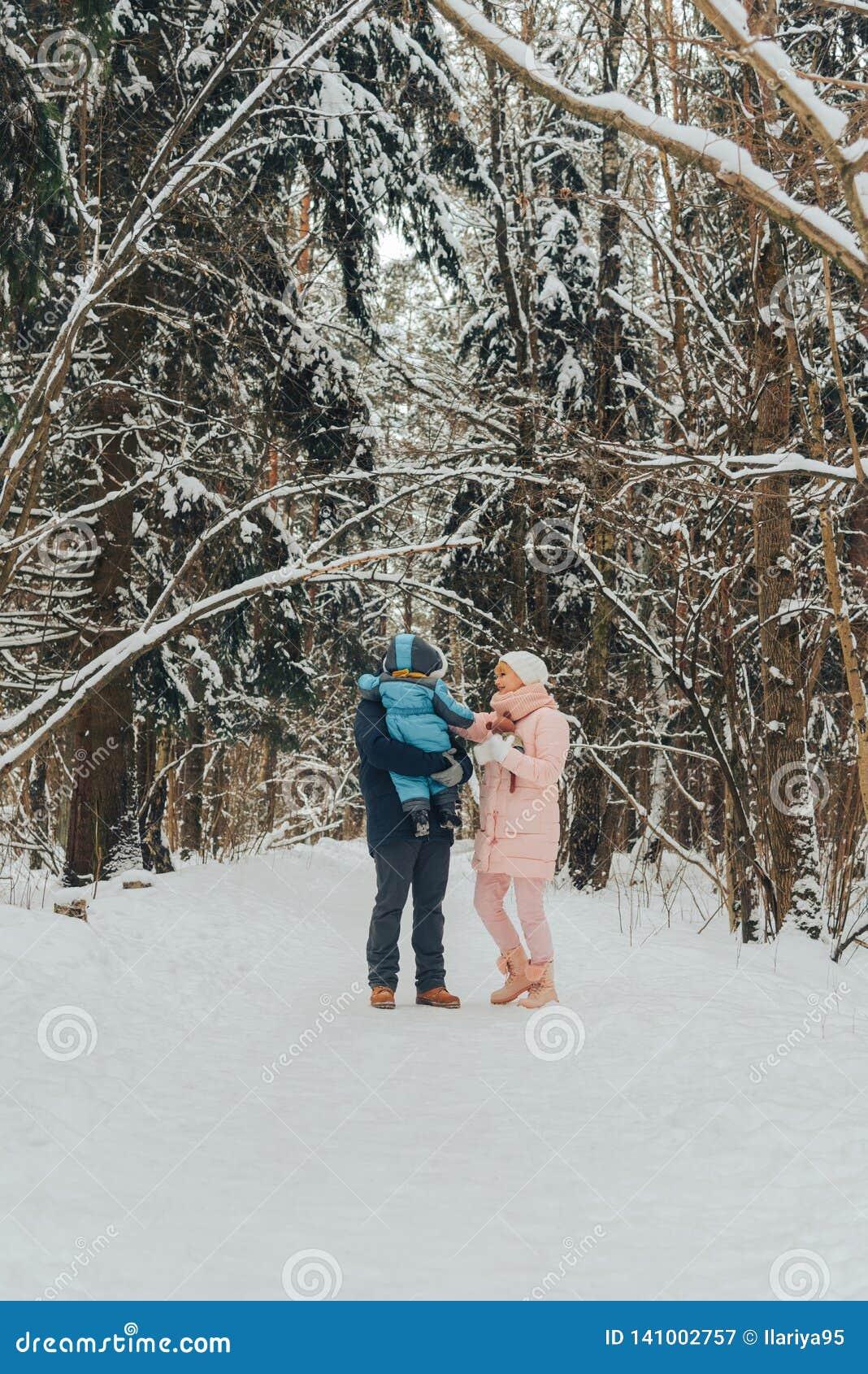 Famiglia di camminata con un bambino La famiglia cammina in natura nell inverno Passeggiata della famiglia di inverno in natura M