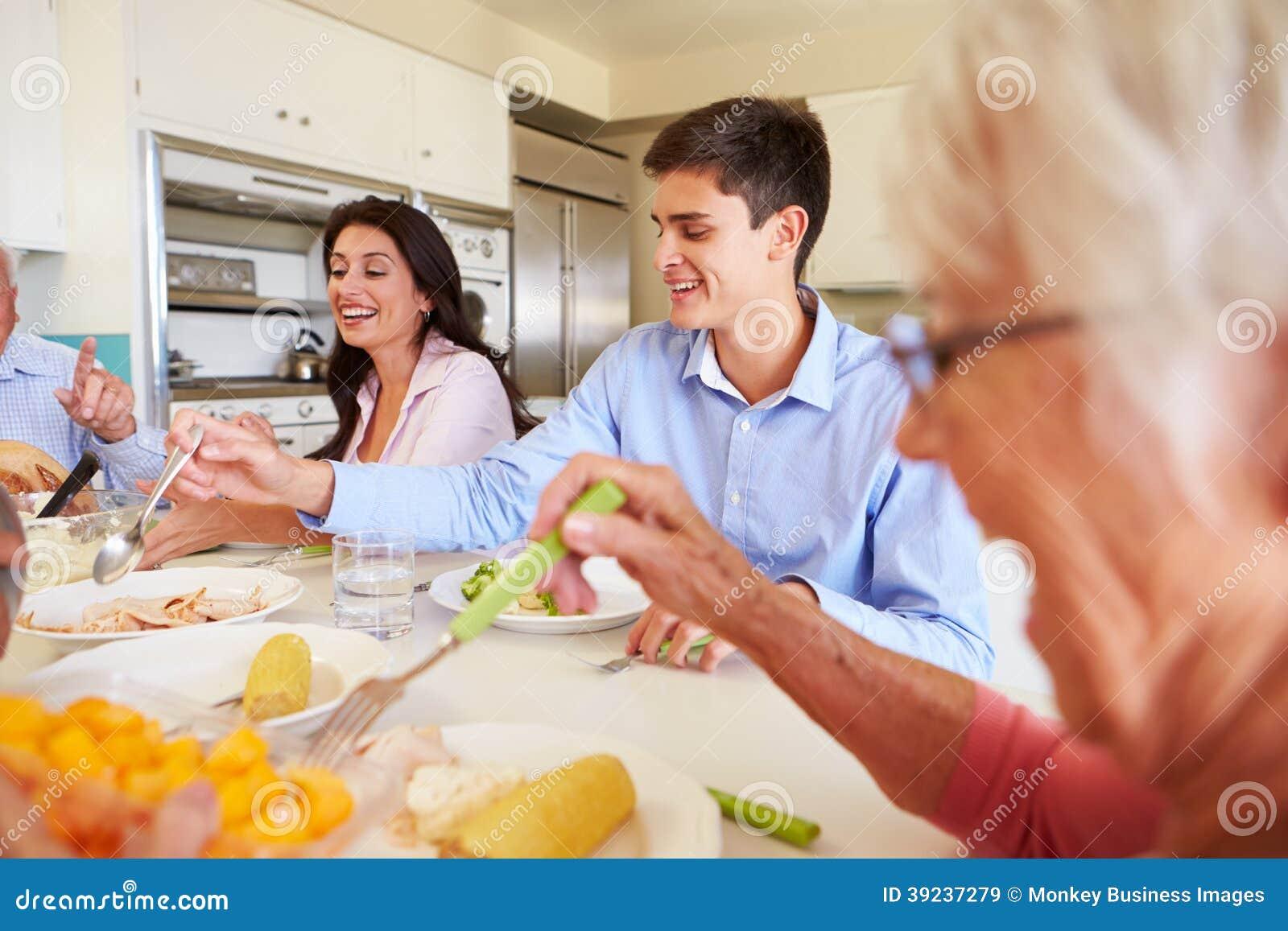 Famiglia di diverse generazioni che si siede intorno alla Tabella che mangia pasto