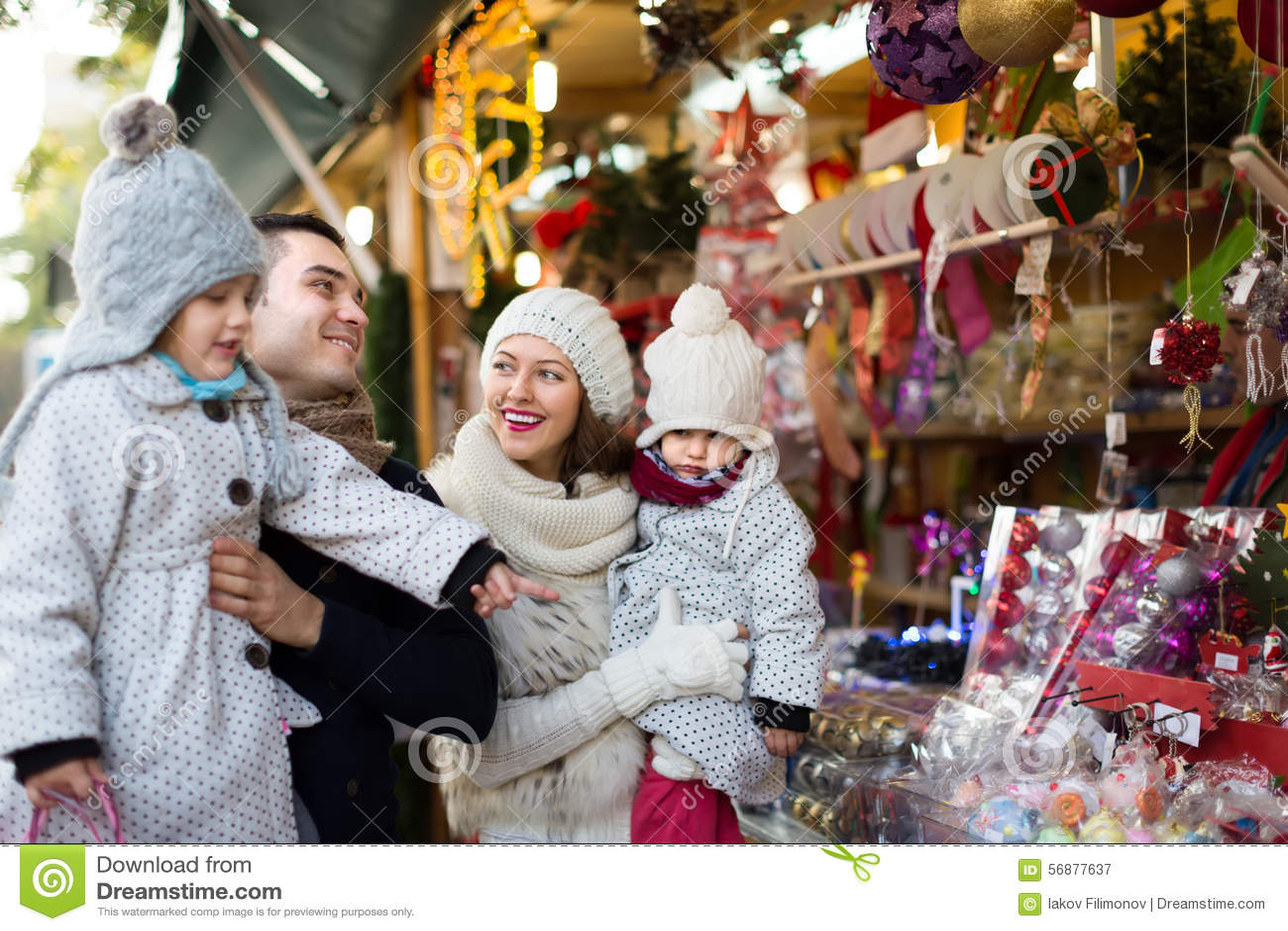 Famiglia di quattro felice al mercato di Natale