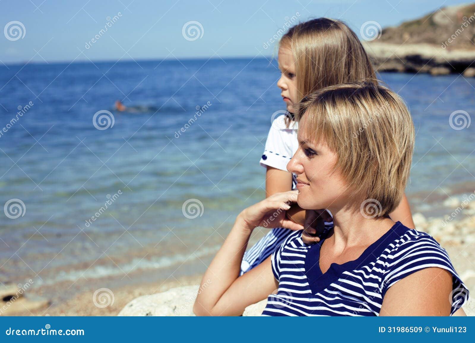 Famiglia divertendosi sulla spiaggia, sulla madre e sulla figlia in mare