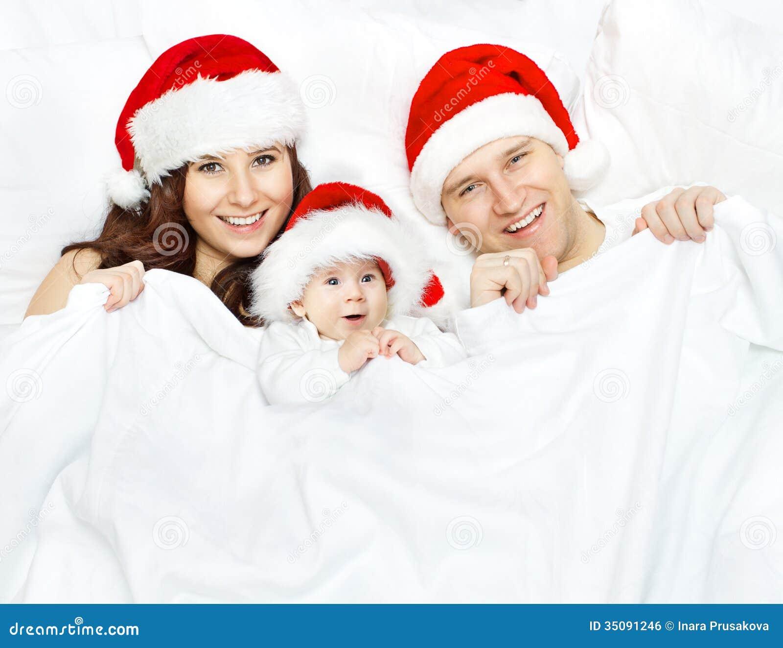 Famiglia e bambino di Natale in cappello di Santa Claus sopra bianco