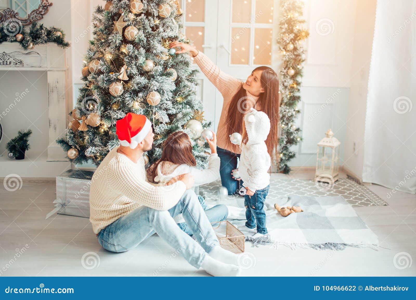 Famiglia felice che decora un albero di Natale con i boubles nel salone
