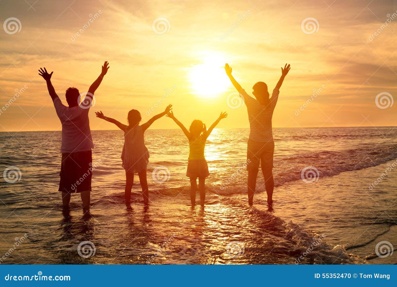 Famiglia felice che guarda il tramonto sulla spiaggia