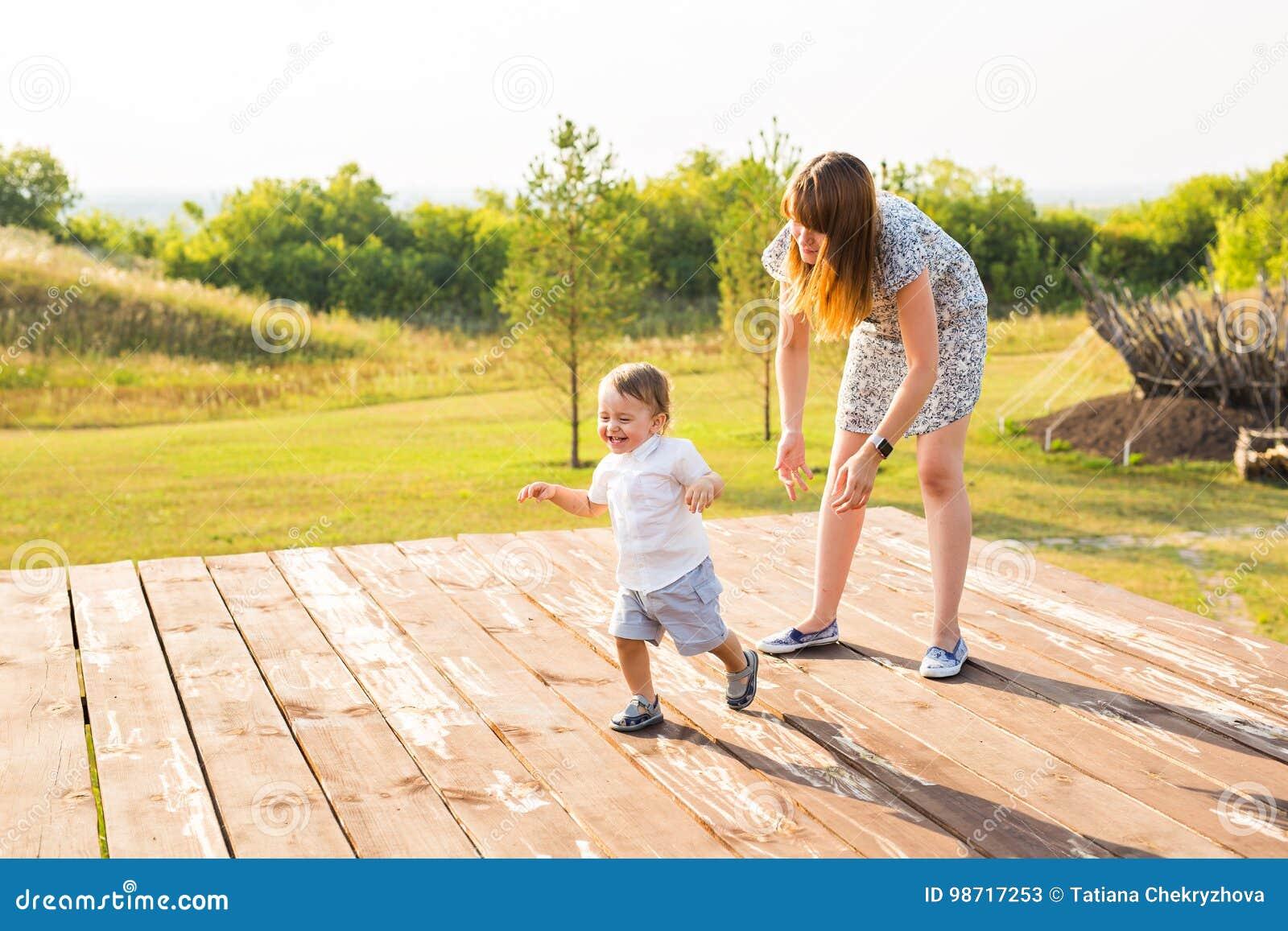 Famiglia felice che ha divertimento neonato e sua madre che giocano all aperto