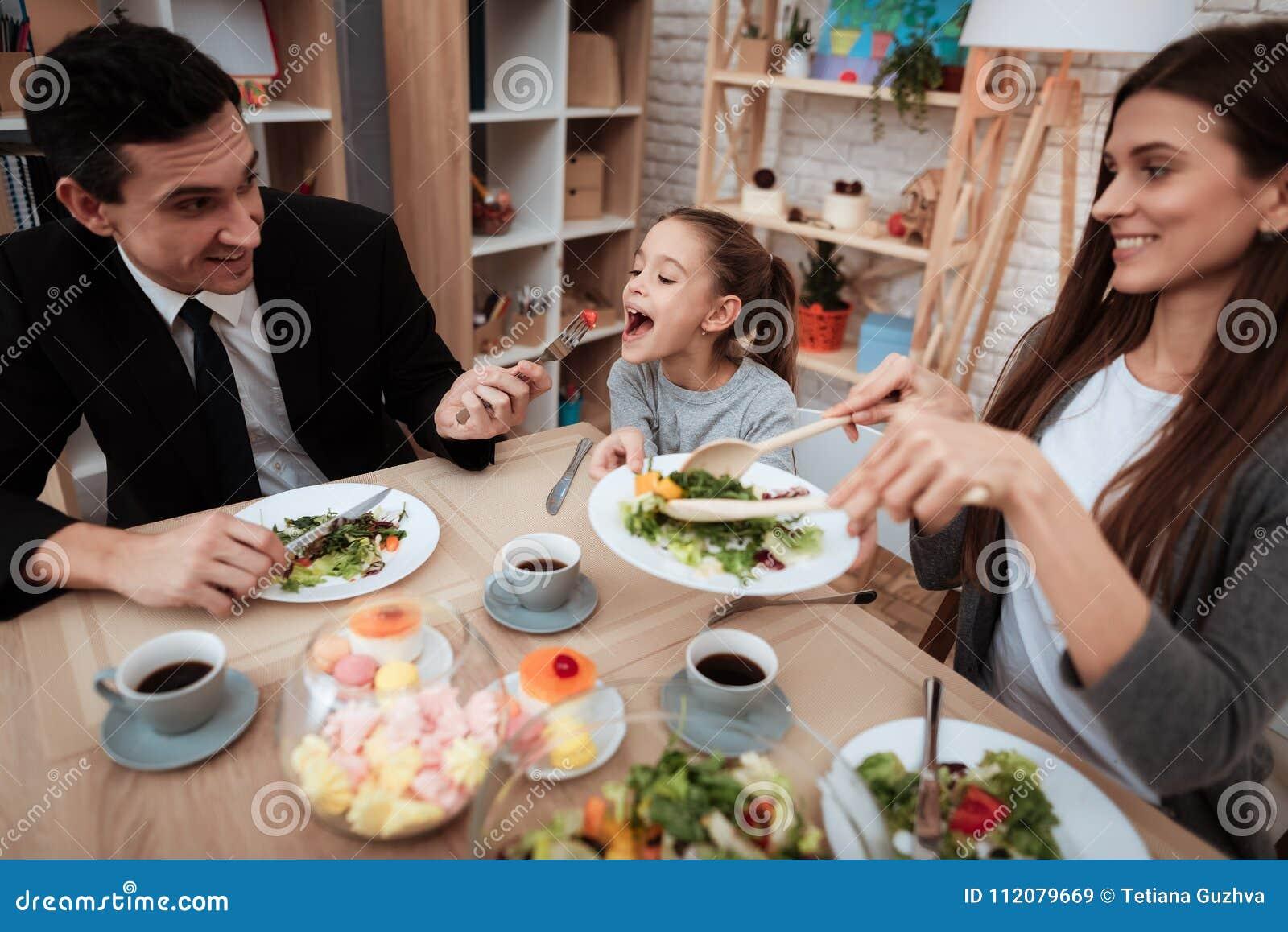 Famiglia felice che mangia insieme i piatti alla tavola Genitori con la loro figlia riunita alla tavola