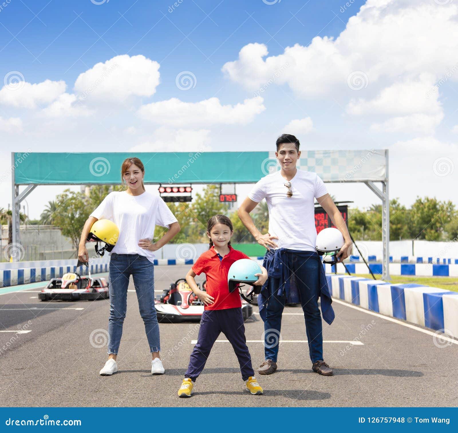 Famiglia felice che sta in movimento la pista di corsa del kart